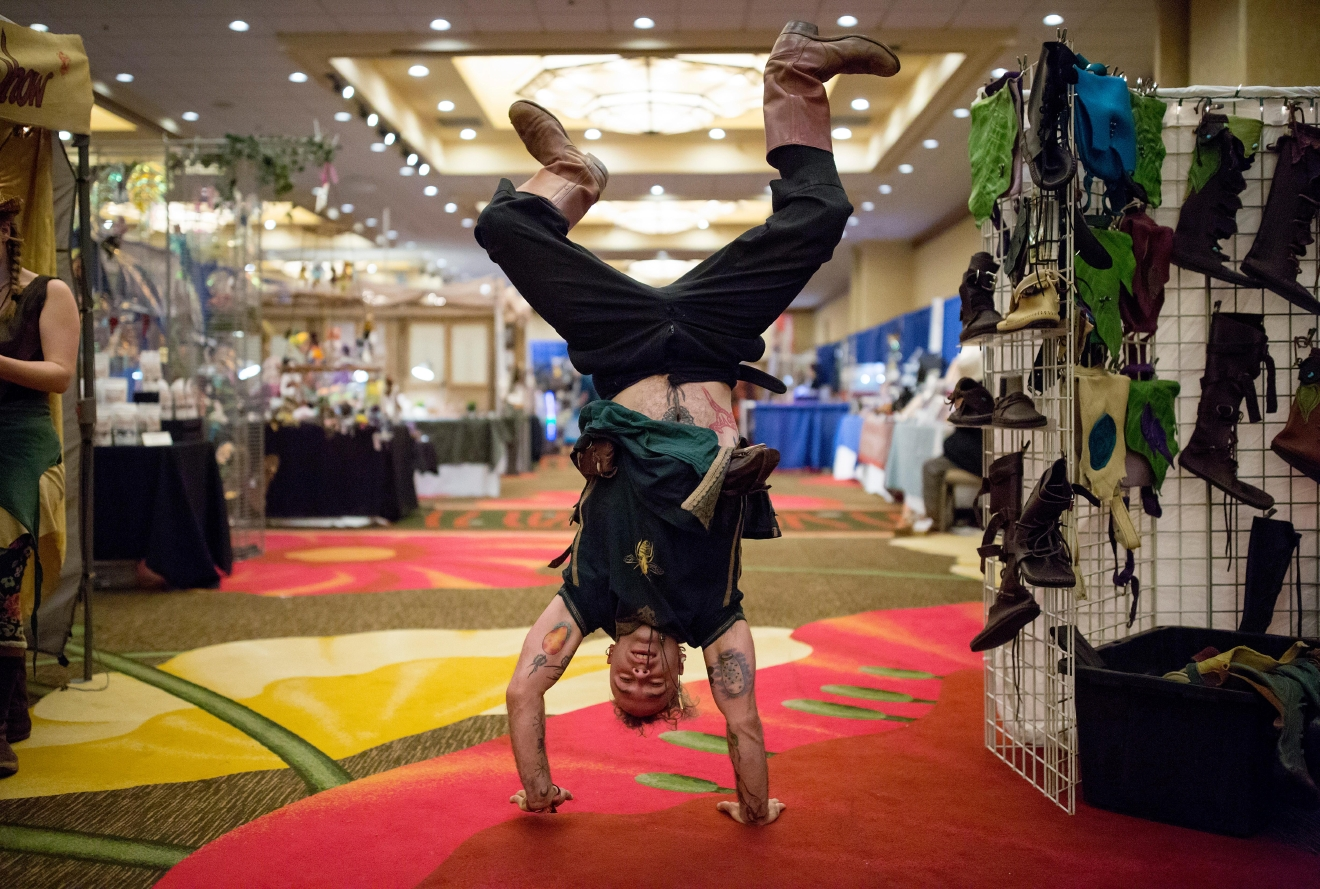 Beekeeper and Medicine Maker Benjamin Pixies does a handstand outside his booth at Mythicworlds Convention and Masquerades. (Sy Bean / Seattle Refined)