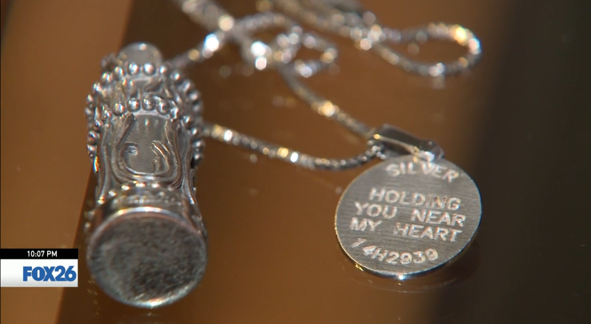 A silver necklace attached to an urn with the name Madelyn engraved.