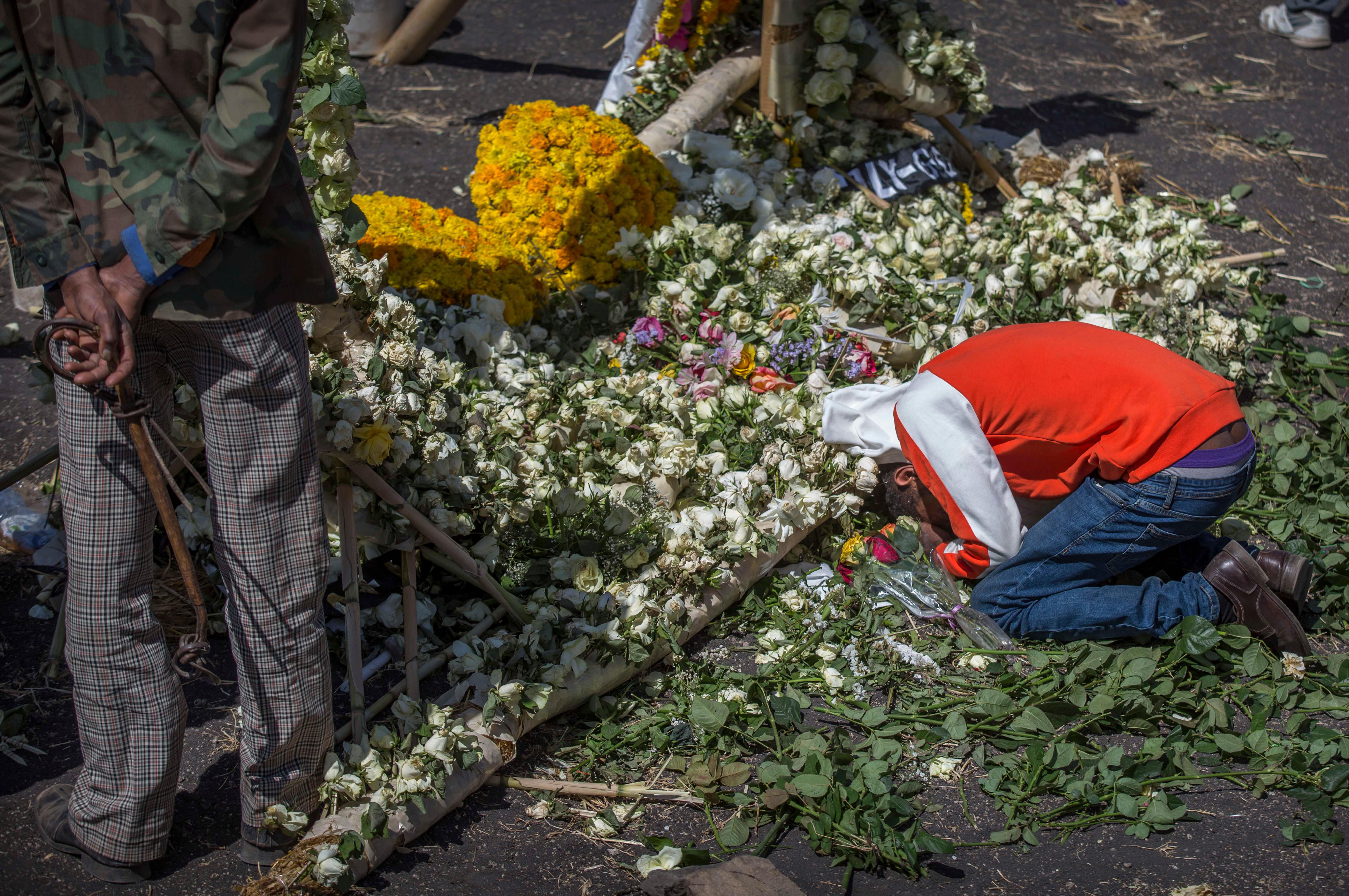 An Ethiopian relative of a crash victim mourns and grieves next to a floral tribute at the scene where the Ethiopian Airlines Boeing 737 Max 8 crashed shortly after takeoff on Sunday killing all 157 on board, near Bishoftu, south-east of Addis Ababa, in Ethiopia Friday, March 15.. (AP Photo/Mulugeta Ayene)