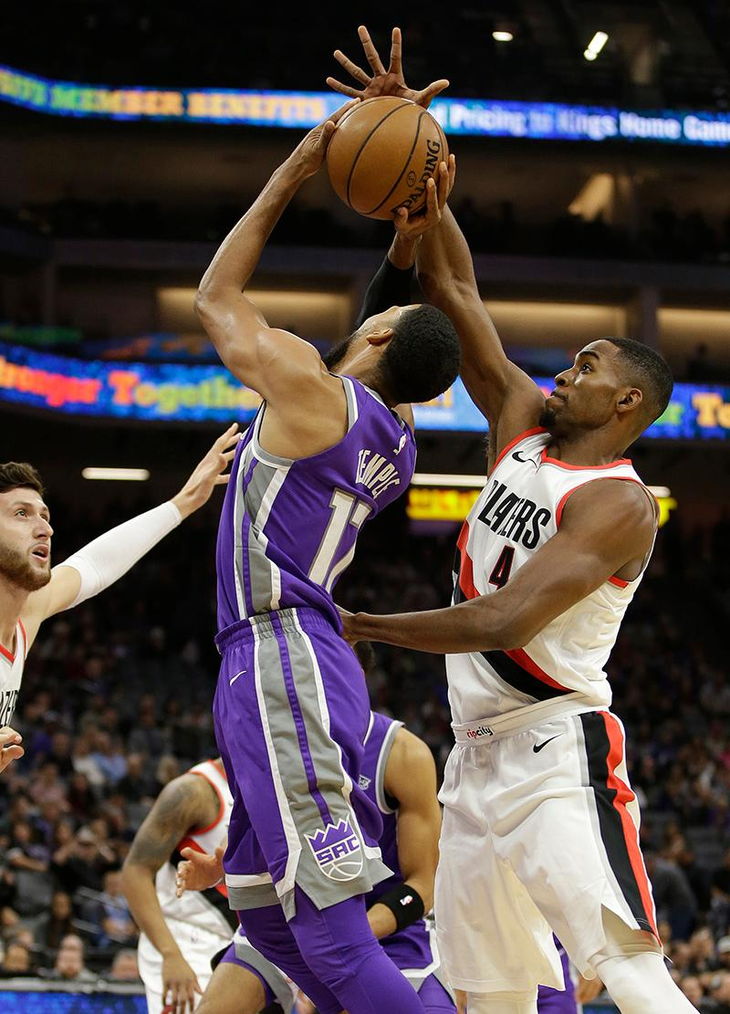Sacramento Kings guard Garrett Temple, center, goes to the basket between Portland Trail Blazers' Jusuf Nurkic, left, of Bosnia, and Maurice Harkless during the first quarter of an NBA basketball game Friday, Nov. 17, 2017, in Sacramento, Calif. (AP Photo/Rich Pedroncelli)
