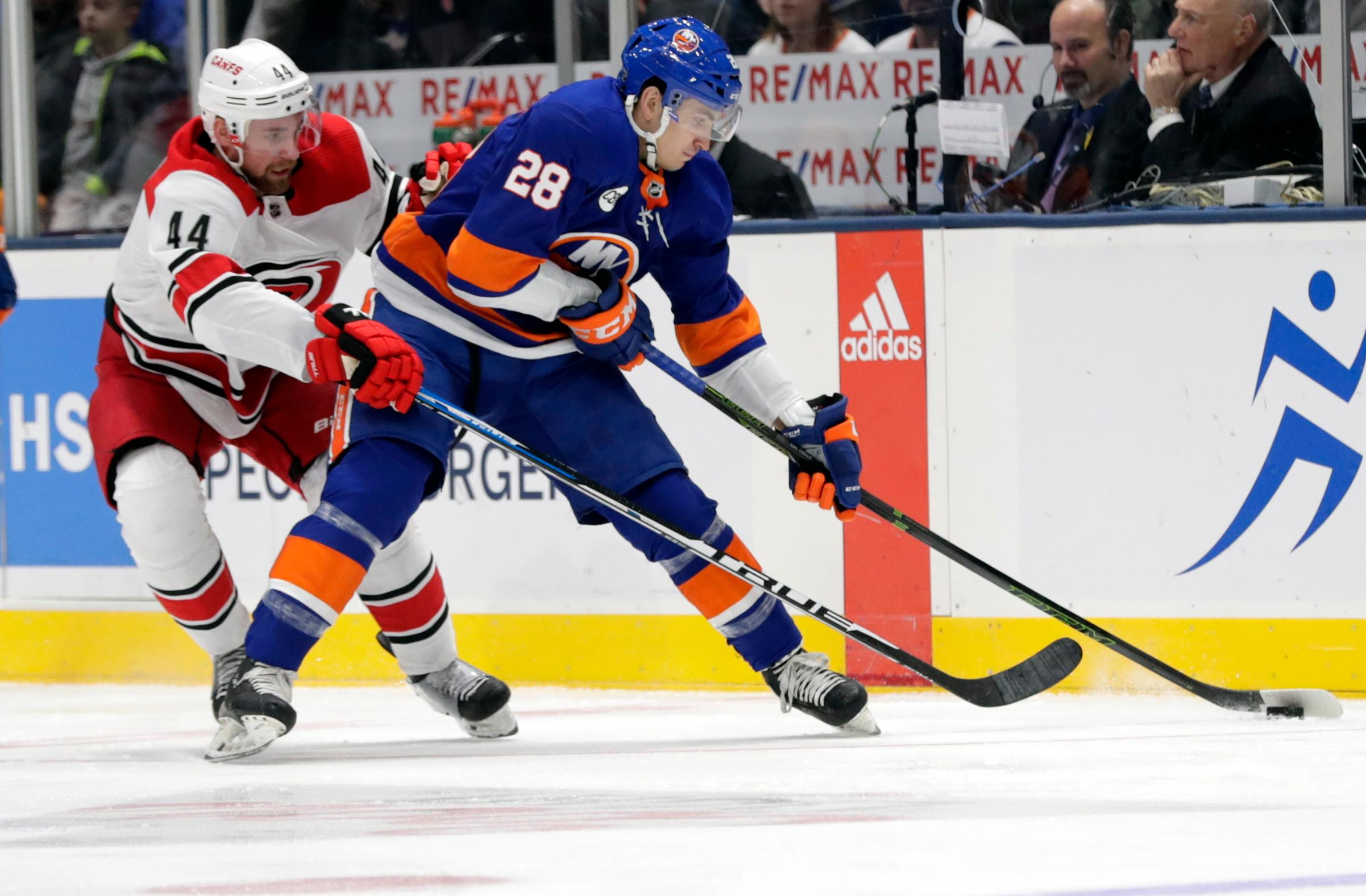 Carolina Hurricanes' Calvin de Haan (44) fights for control of the puck with New York Islanders' Michael Dal Colle (28) during the first period of an NHL hockey game Tuesday, Jan. 8, 2019, in New York. (AP Photo/Frank Franklin II)