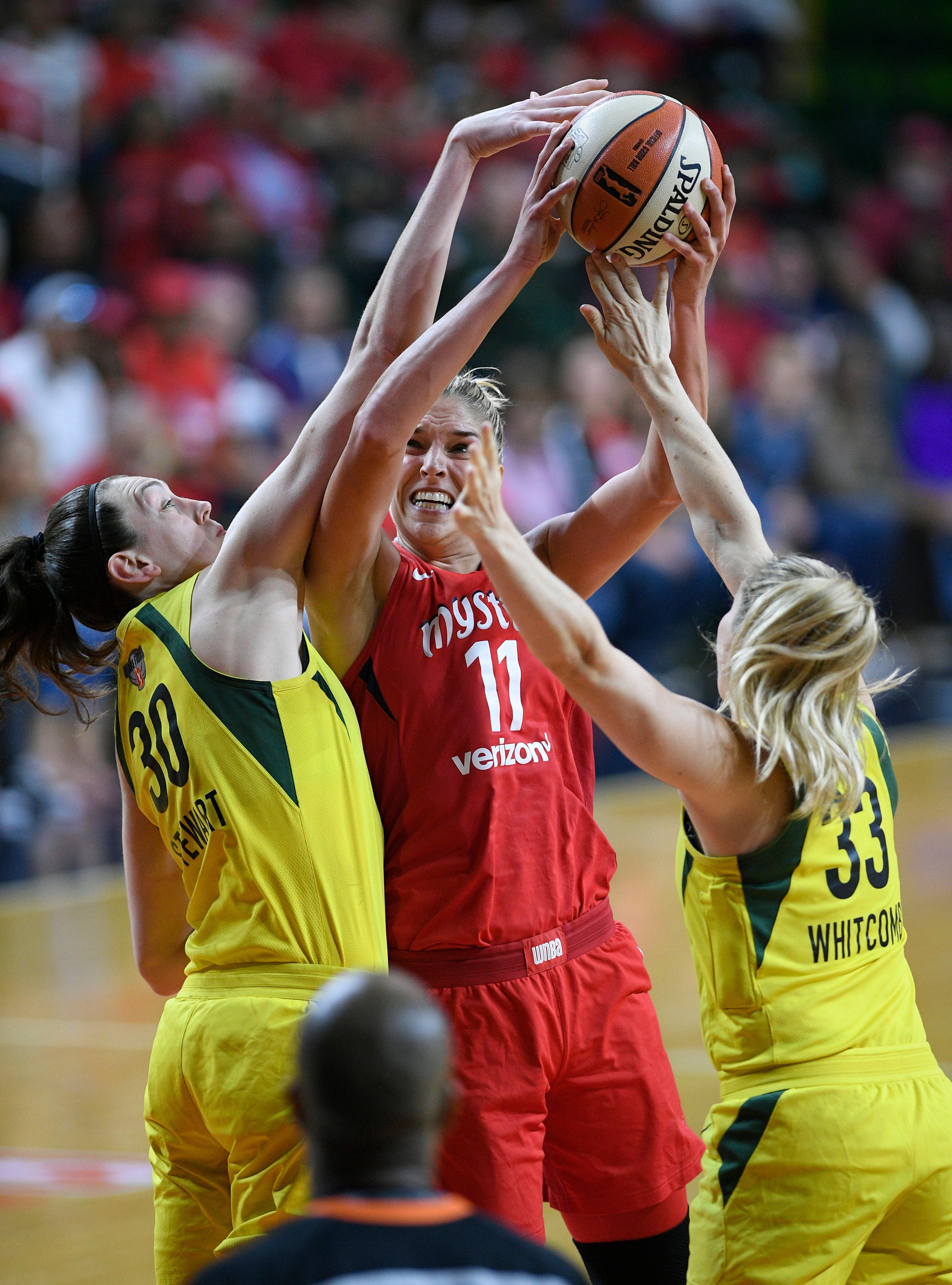 Washington Mystics forward Elena Delle Donne (11) goes to the basket as she was fouled by Seattle Storm forward Breanna Stewart (30) during the second half of Game 3 of the WNBA basketball finals, Wednesday, Sept. 12, 2018, in Fairfax, Va. Also seen is Storm guard Sami Whitcomb (33). The Storm won 98-82 and the title. (AP Photo/Nick Wass)