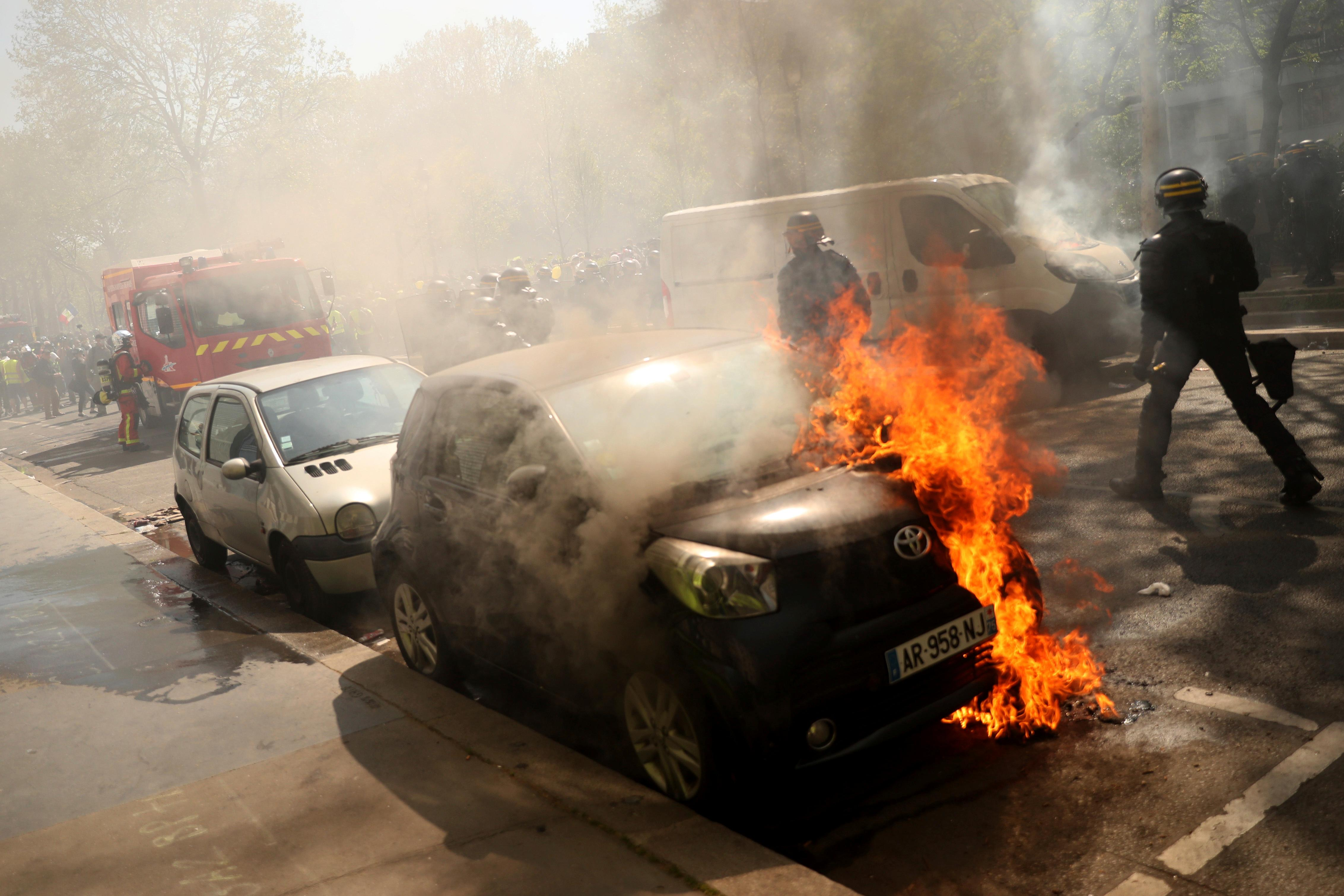 A car is set alight during a yellow vest demonstration in Paris, Saturday, April 20, 2019. French yellow vest protesters are marching anew to remind the government that rebuilding the fire-ravaged Notre Dame Cathedral isn't the only problem the nation needs to solve. (AP Photo/Francisco Seco)