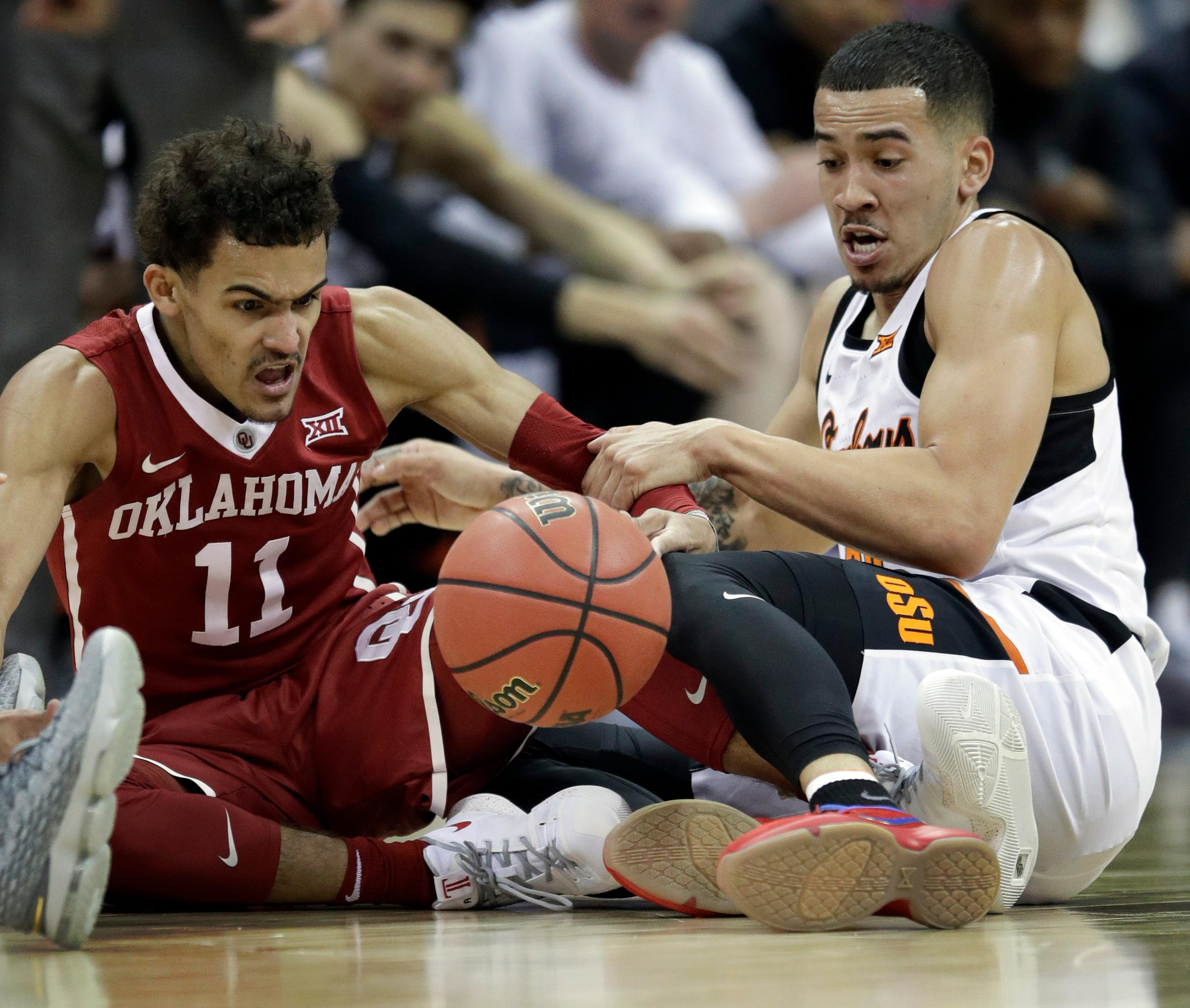 Oklahoma guard Trae Young (11) goes to the floor for a loose ball with Oklahoma State guard Jeffrey Carroll, right, during the first half of an NCAA college basketball game in first round of the Big 12 men's tournament in Kansas City, Mo., Wednesday, March 7, 2018. (AP Photo/Orlin Wagner)