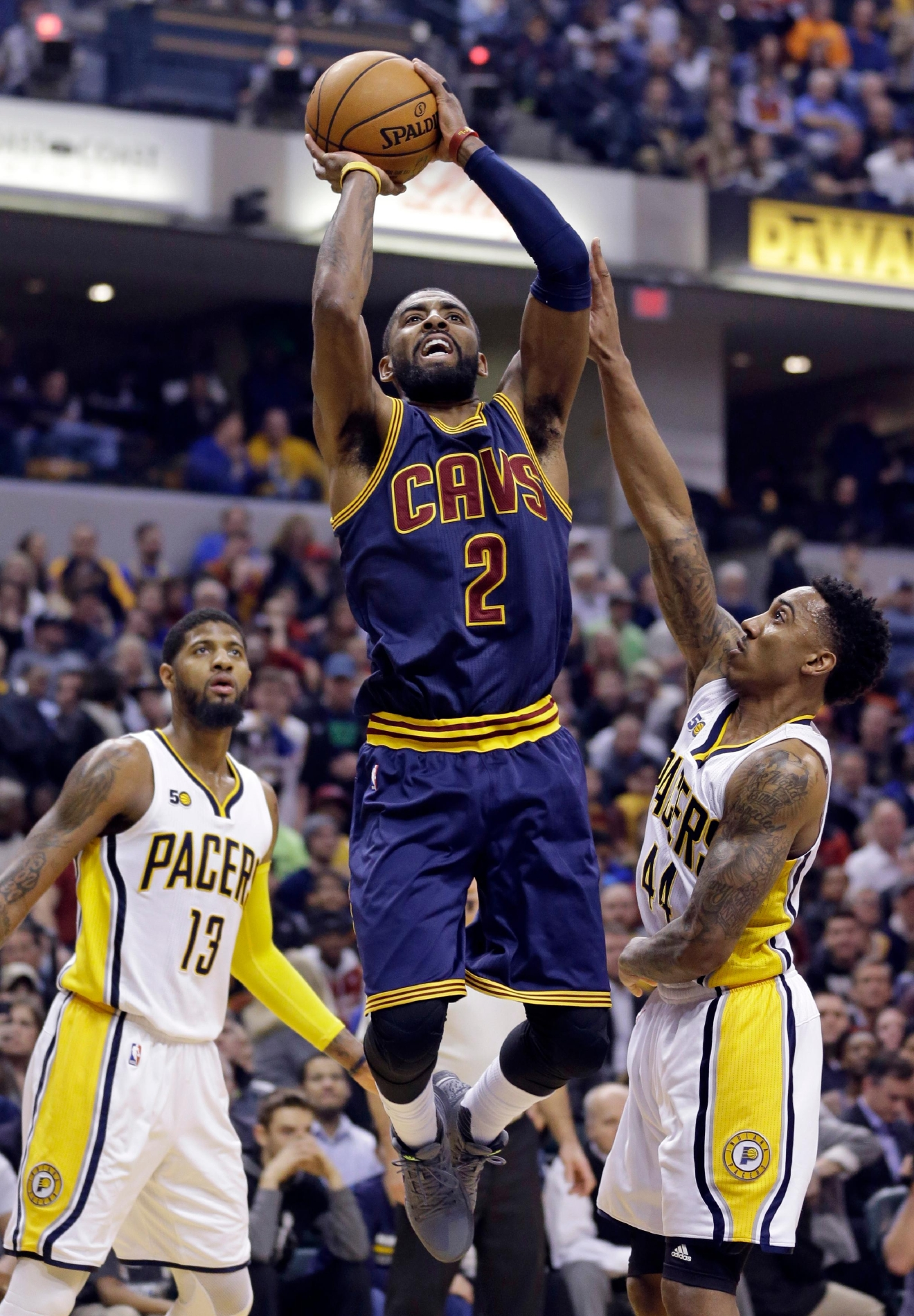 Cleveland Cavaliers guard Kyrie Irving (2) shoots between Indiana Pacers forward Paul George (13) and guard Jeff Teague (44) during the first half of an NBA basketball game in Indianapolis, Wednesday, Feb. 8, 2017. (AP Photo/Michael Conroy)