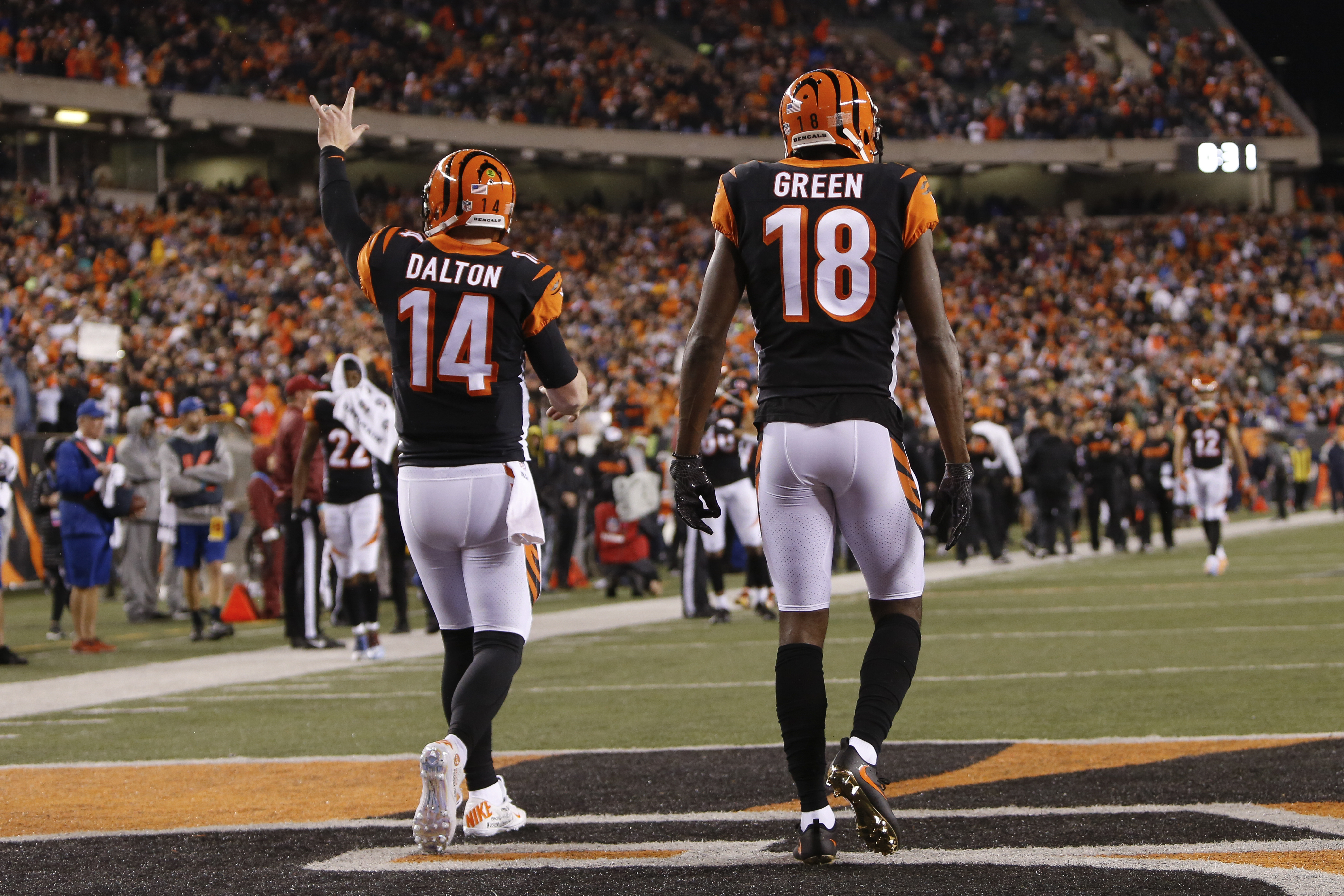 Cincinnati Bengals wide receiver A.J. Green (18) walks back to the sideline with quarterback Andy Dalton (14) after scoring a touchdown in the first half of an NFL football game against the Pittsburgh Steelers, Monday, Dec. 4, 2017, in Cincinnati. (AP Photo/Frank Victores)