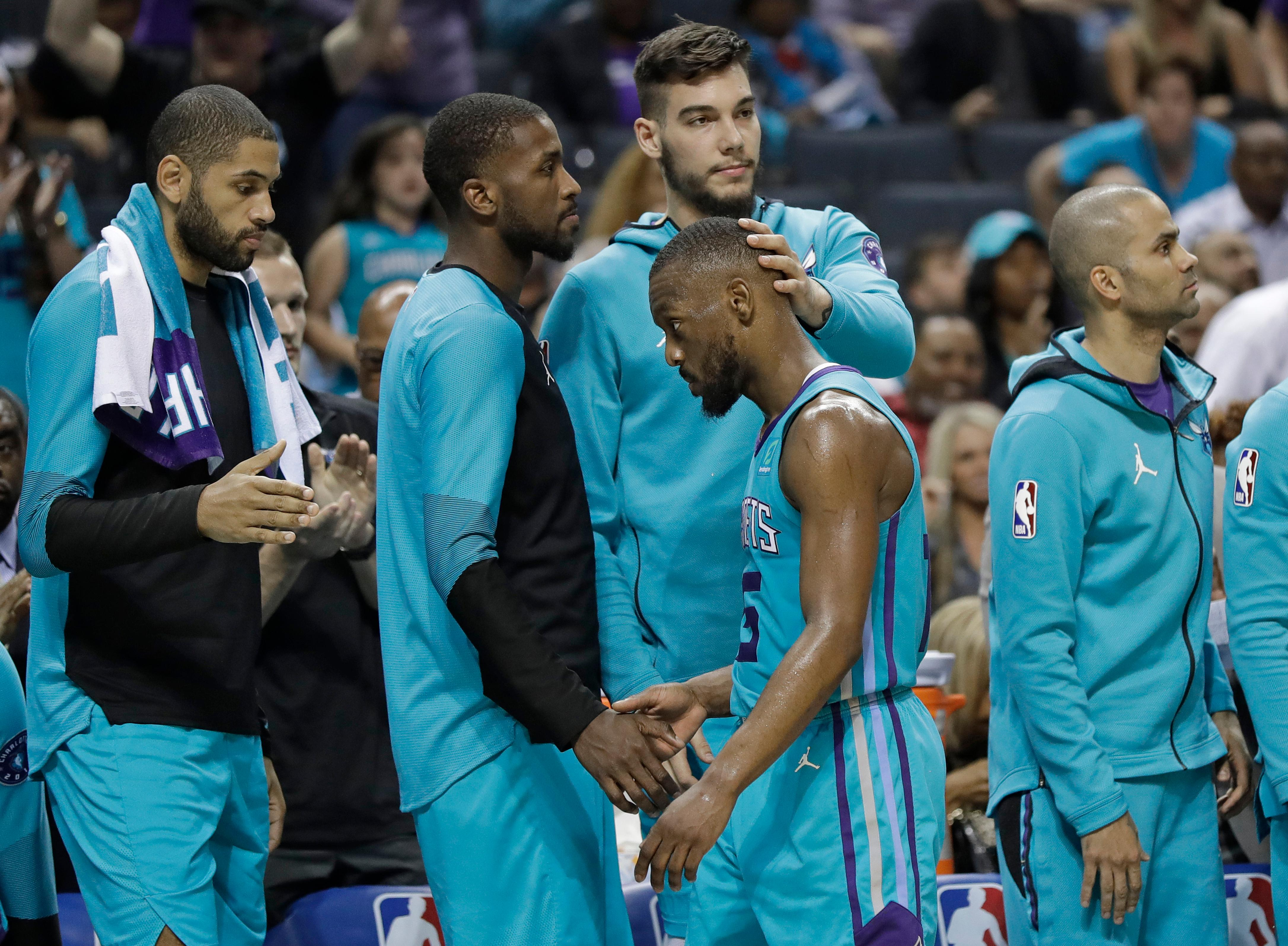 File-THis April 10, 2019, file photo shows Charlotte Hornets' Kemba Walker, center, being greeted by teammates as he leaves the NBA basketball game against the Orlando Magic late in the second half, in Charlotte, N.C. A person with knowledge of the situation says Kemba Walker has told the Charlotte Hornets of his intention to sign with the Boston Celtics once the NBA's offseason moratorium ends July 6. Walker is planning to meet with the Celtics on Sunday, June 30, 2019, to discuss and likely finalize a four-year, $141 million deal, according to the person who spoke to The Associated Press on condition of anonymity because neither Walker nor the Hornets publicly revealed any details. (AP Photo/Chuck Burton,File)