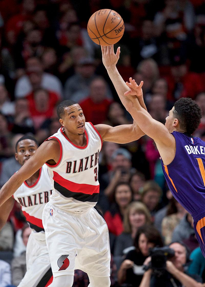 Portland Trail Blazers guard C.J. McCollum, left, knocks the ball away from Phoenix Suns guard Devin Booker during the first half of an NBA basketball game in Portland, Ore., Tuesday, Nov. 8, 2016. (AP Photo/Craig Mitchelldyer)
