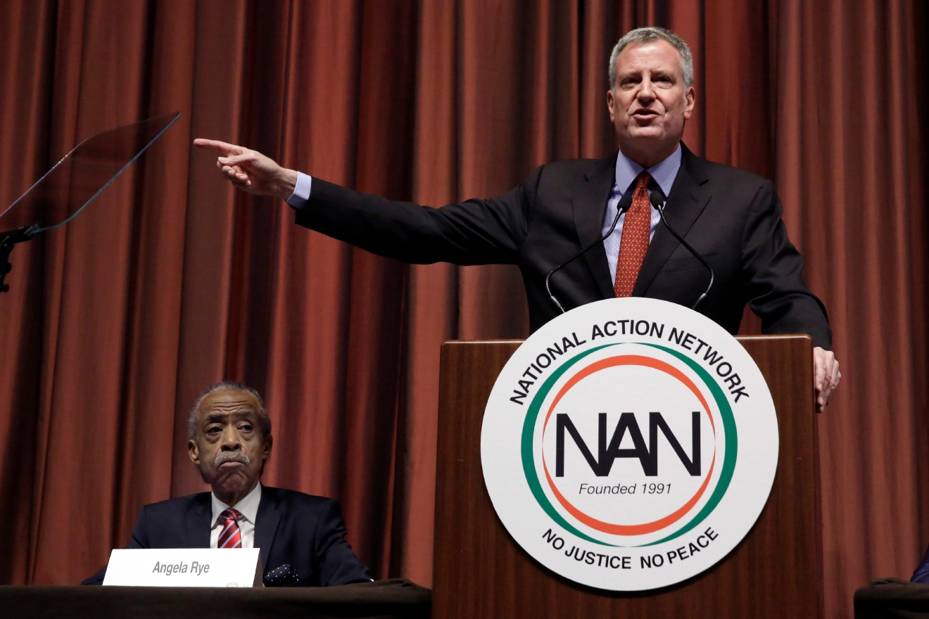 New York Mayor Bill de Blasio delivers his remarks during the 25th annual National Action Network convention, in New York, Wednesday, April 13, 2016. Seated at left is the Rev. Al Sharpton. (AP Photo/Richard Drew)