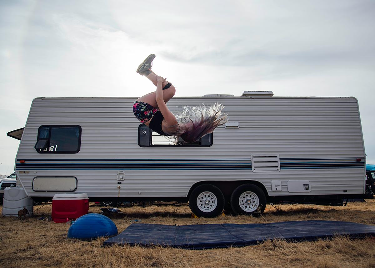 Lauren Gilman practices her competitive gymnatsic skills as a way to keep herself entertained at Solar Port, the makeshift campground at the Madras Airport. Photo by Cheyenne Thorpe, Oregon News Lab