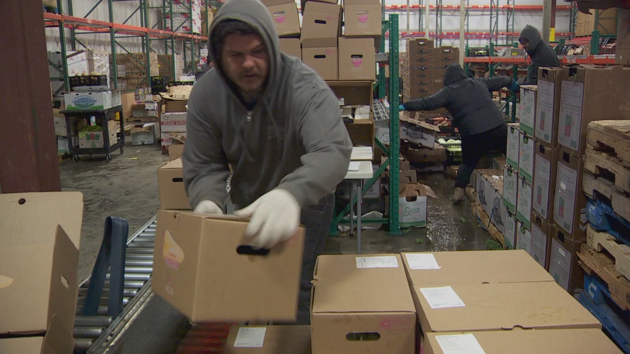 Workers fill boxes of produce for home delivery drivers. (KATU)<p></p>