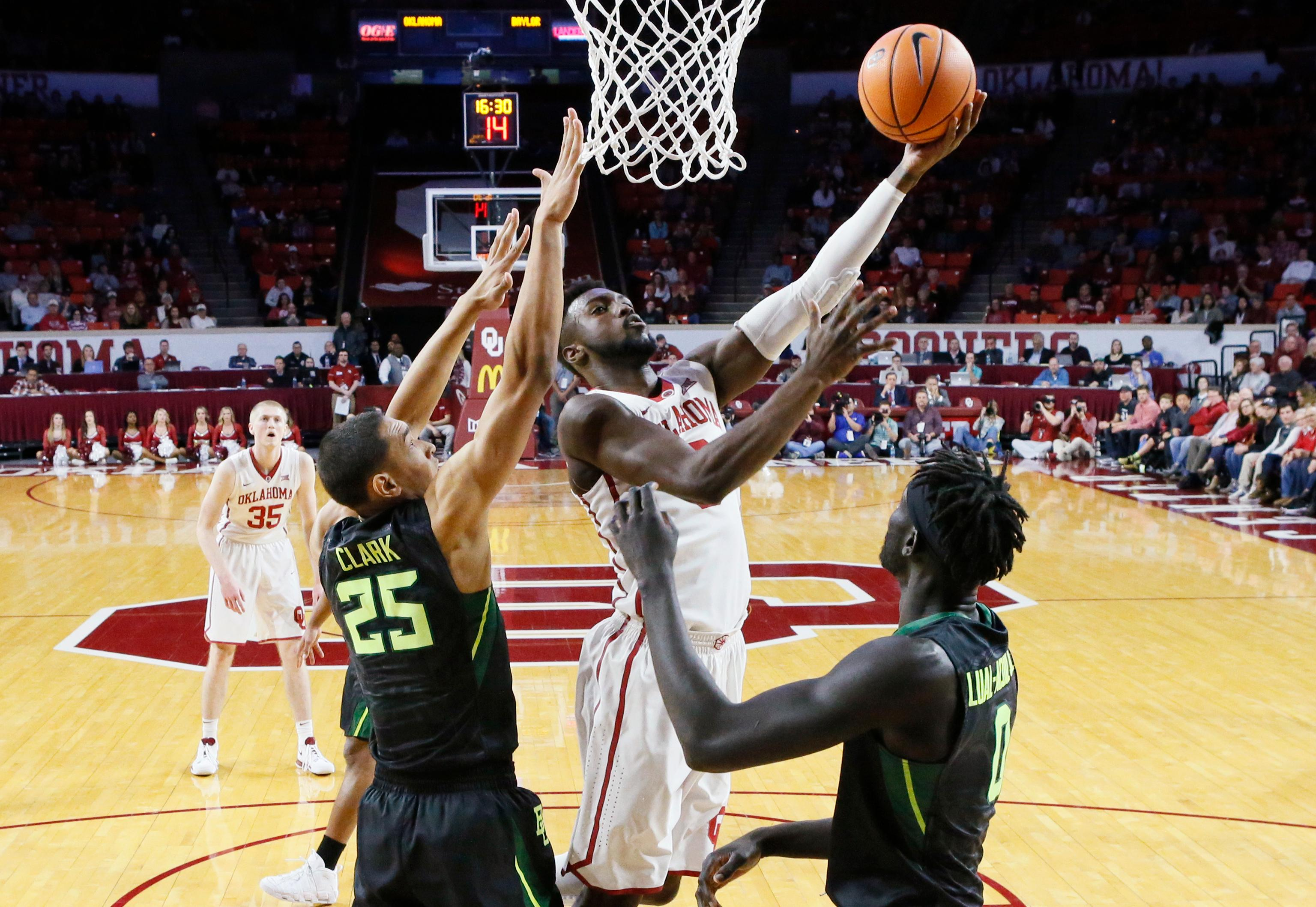 Oklahoma forward Khadeem Lattin, center, shoots between Baylor forward Tristan Clark (25) and forward Jo Lual-Acuil Jr., right, during the first half of an NCAA college basketball game in Norman, Okla., Tuesday, Jan. 30, 2018. (AP Photo/Sue Ogrocki)