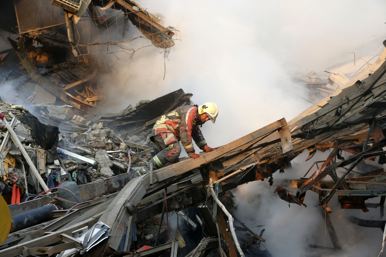 A firefighter works during the operations removing debris of the Plasco building where collapsed after engulfed by a fire, in central Tehran, Iran, Thursday, Jan. 19, 2017. A high-rise building in Tehran engulfed by fire collapsed on Thursday. The disaster struck the Plasco building, an iconic structure in central Tehran just north of the Iranian capital's sprawling bazaar. Firefighters, soldiers and other emergency responders dug through the rubble, looking for survivors. (AP Photo/Vahid Salemi)