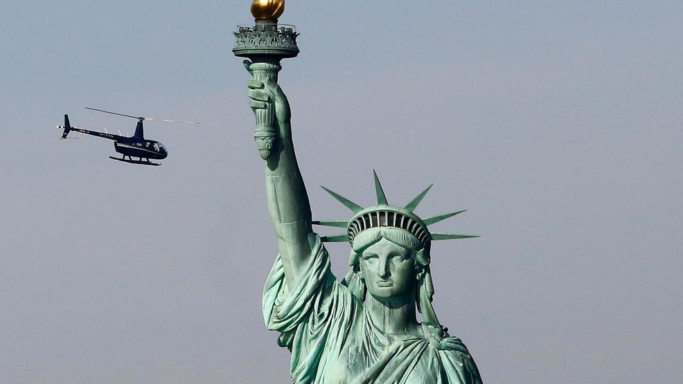watch climber on statue of liberty base after anti ice banner hung