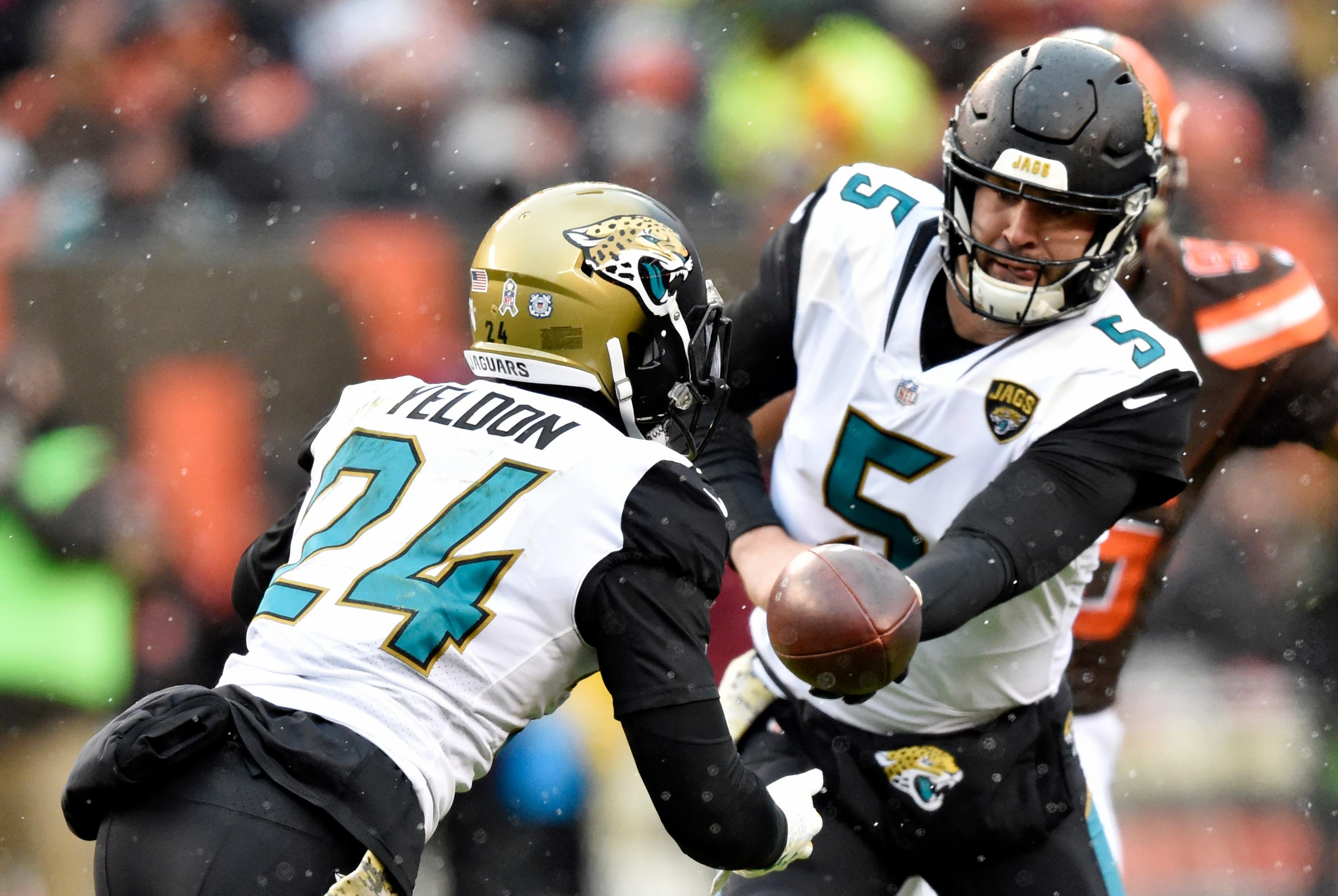 Jacksonville Jaguars quarterback Blake Bortles (5) hands the ball off to running back T.J. Yeldon (24) in the first half of an NFL football game against the Cleveland Browns, Sunday, Nov. 19, 2017, in Cleveland. (AP Photo/David Richard)
