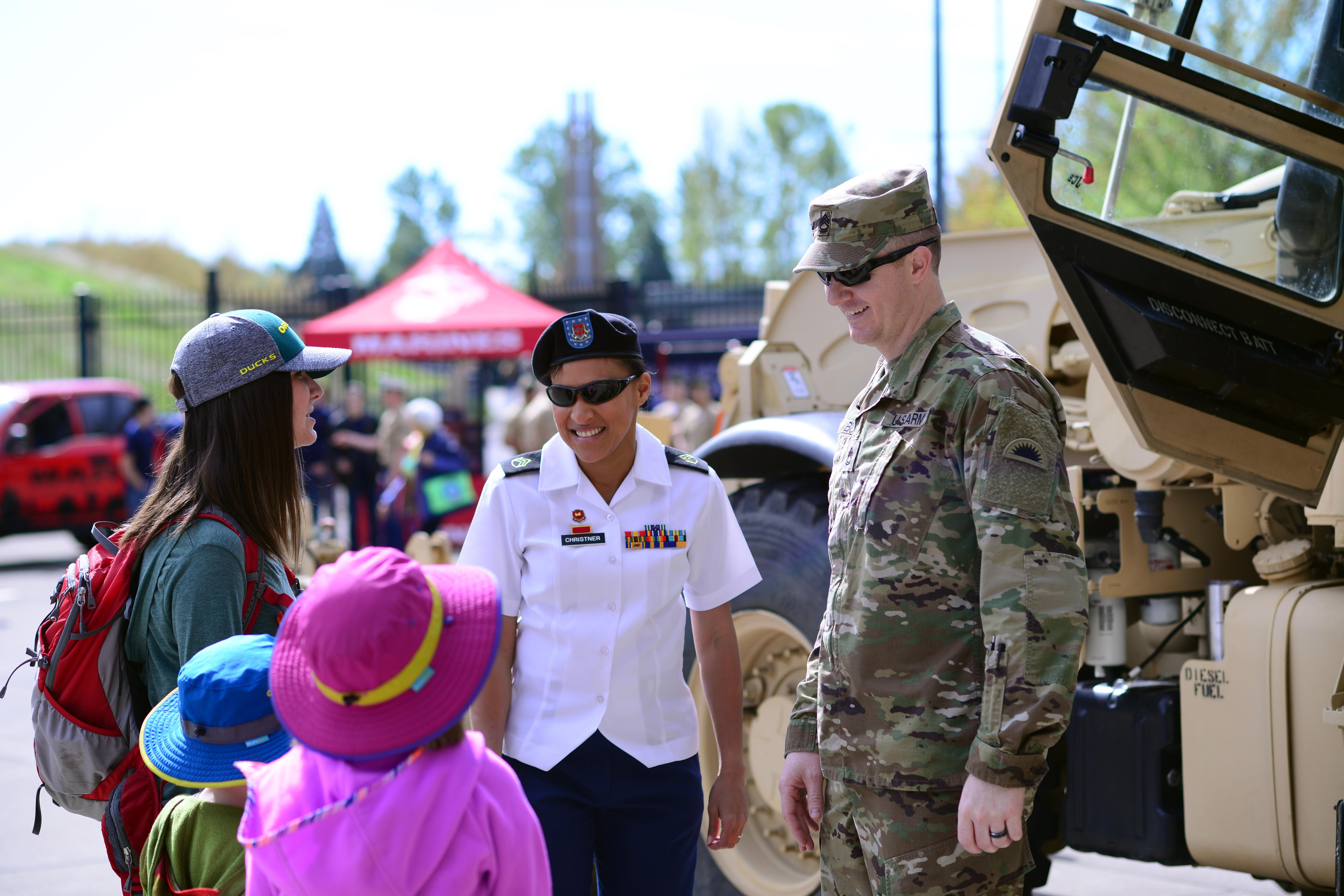 Oregon National Guard Soldiers greet fans in front of Autzen Stadium where military equipment was on display for the University of Oregon's Spring Game, April 29, 2017, in Eugene, Oregon. Veterans from every branch of service participated in Military Appreciation Day activities during the game. (Photo by Sgt. 1st Class April Davis, Oregon Military Department Public Affairs)