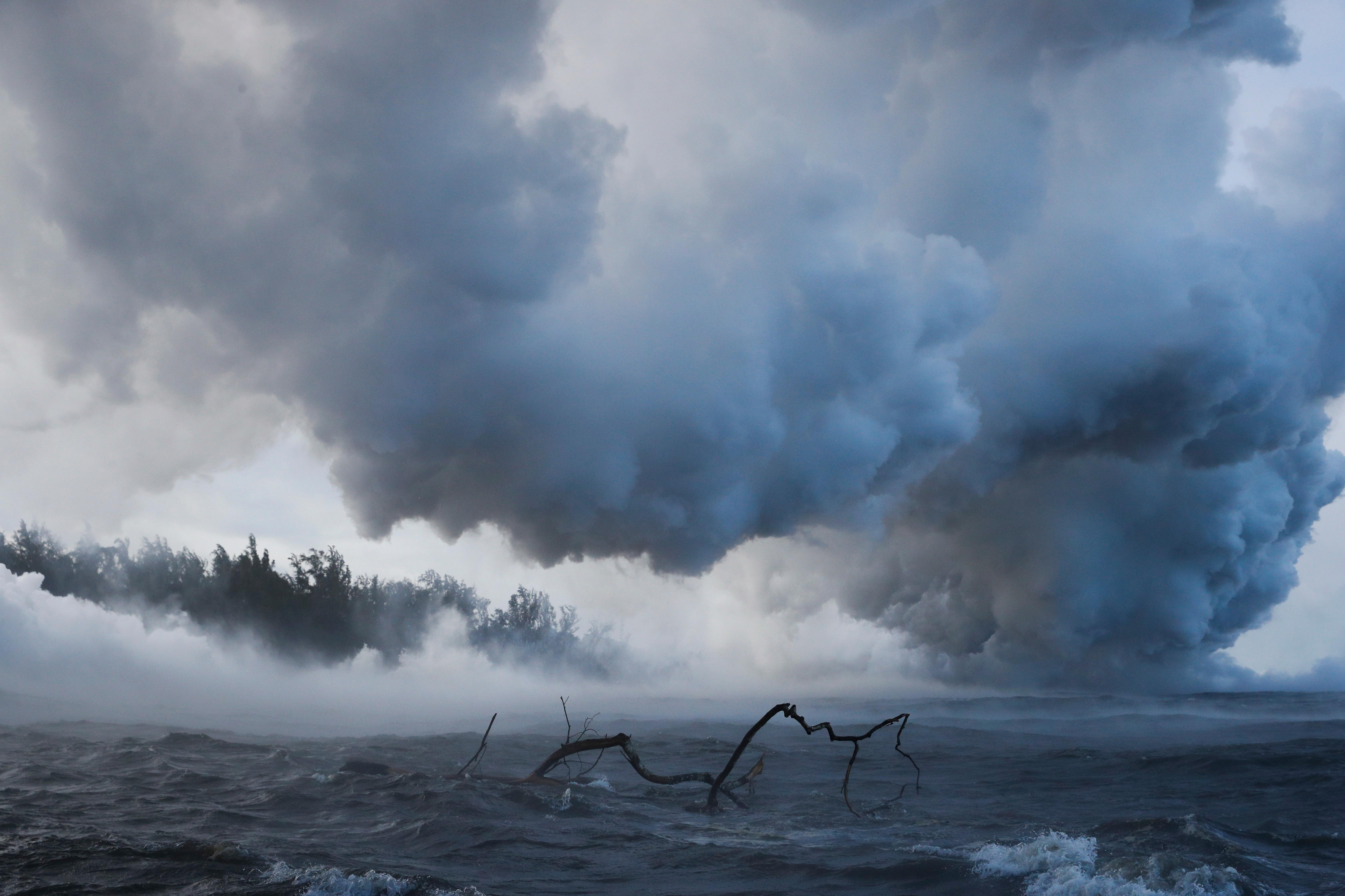 Plumes of steam rise as lava enters the ocean near Pahoa, Hawaii Sunday, May 20, 2018. Kilauea volcano that is oozing, spewing and exploding on Hawaii's Big Island has gotten more hazardous in recent days, with rivers of molten rock pouring into the ocean Sunday and flying lava causing the first major injury. (AP Photo/Jae C. Hong)