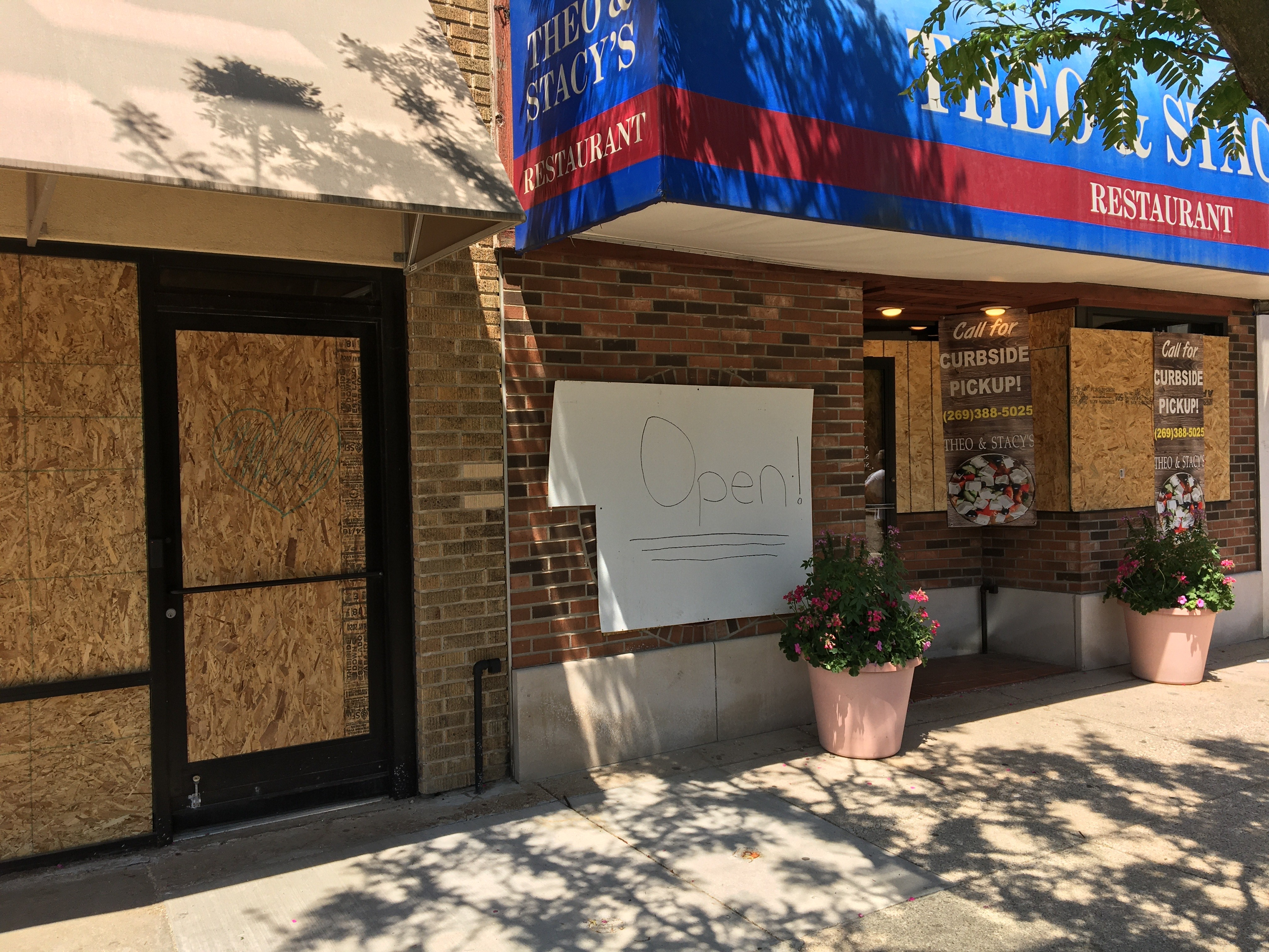 Theo & Stacey's downtown boarded up the windows but was remaining open for a while Tuesday afternoon, ahead of a mandatory curfew set by the city to curb an expected second night of looting and vandalism.  (WWMT/Manny Revilla)