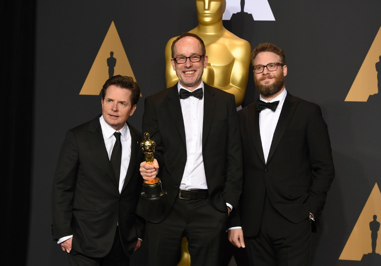 "John Gilbert, center, winner of the award for best film editing for ""Hacksaw Ridge,"" poses in the press room with Michael J. Fox, left, and Seth Rogen, right, at the Oscars on Sunday, Feb. 26, 2017, at the Dolby Theatre in Los Angeles. (Photo by Jordan Strauss/Invision/AP)"