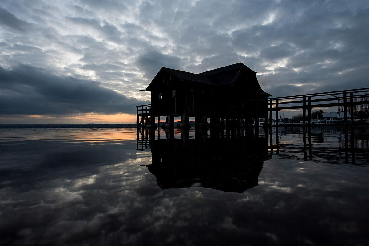 In this Nov. 12, 2016 picture dark clouds and a landing stage with boat house are mirrored  in  Lake Ammersee ,  near Inning am Ammersee, southern Germany. (Lukas Barth/dpa via AP)