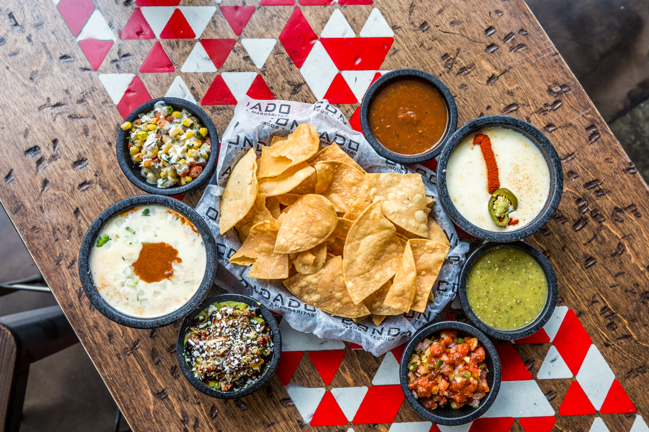 Chips with roja salsa, queso blanco, verde salsa, pineapple salsa, tuscan guac, dirty queso, and corn salsa / Image: Catherine Viox{ }// Published: 6.9.19