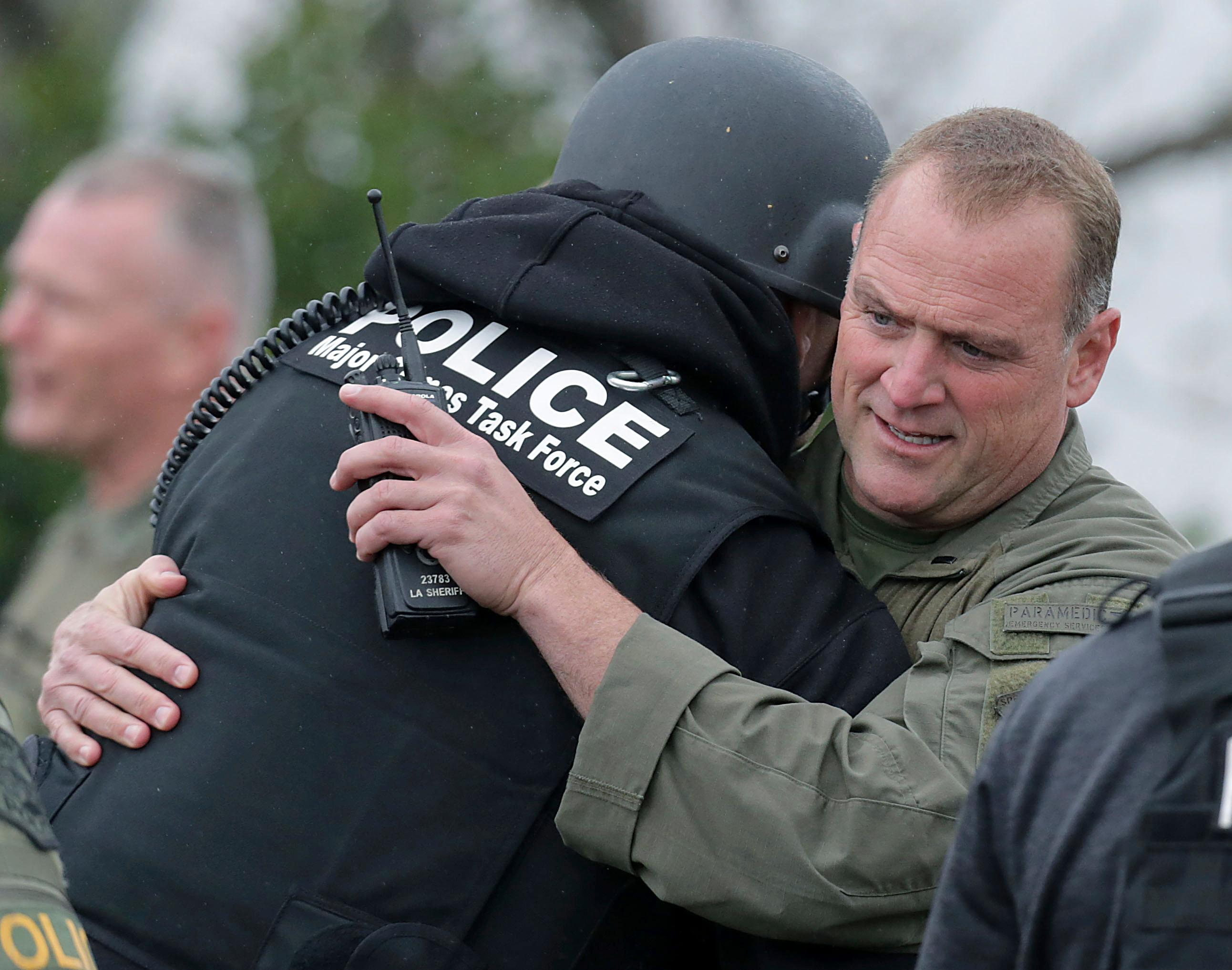 Pomona Police officers hug after arresting the stand-off suspect in an apartment Saturday, March 10, 2018, in Pomona, Calif. The gunman who shot two California police officers, killing one of them, was arrested Saturday after barricading himself in an apartment and holding a SWAT team at bay for more than 15 hours, authorities said. (Terry Pierson/The Press-Enterprise via AP)