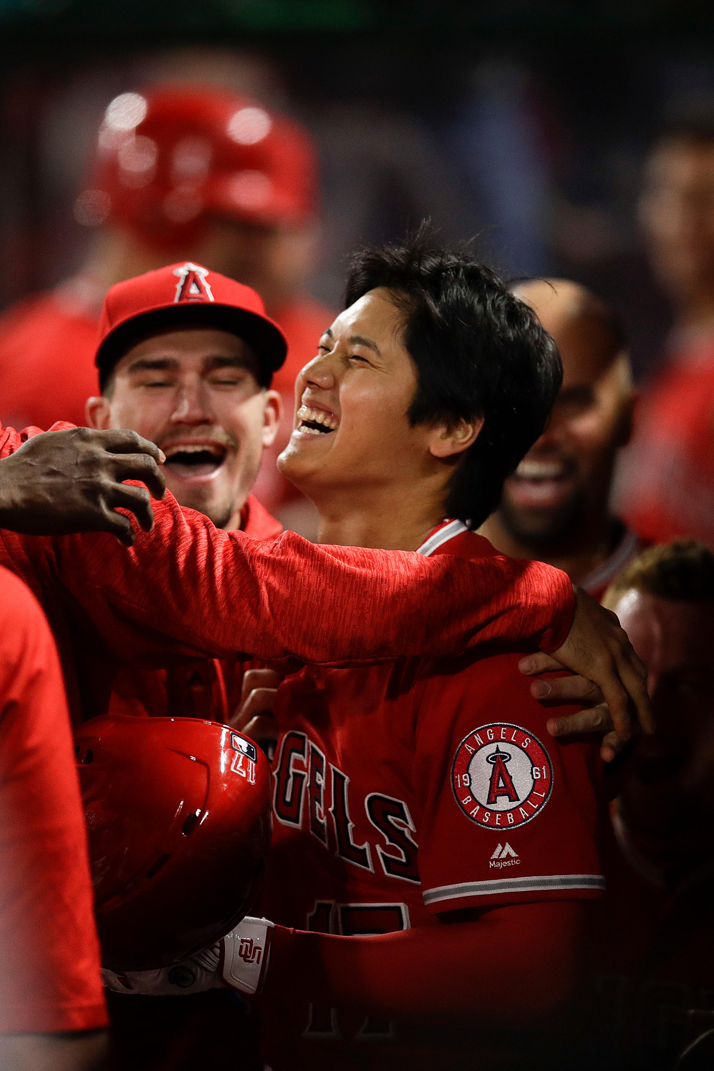 Los Angeles Angels starting pitcher Shohei Ohtani, of Japan, celebrates his three-run home run in the dugout during the first inning of a baseball game against the Cleveland Indians, Tuesday, April 3, 2018, in Anaheim, Calif. (AP Photo/Jae C. Hong)