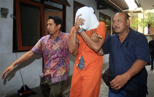 Indonesian police officers escort Tommy Schaefer, center, covering his face, to a hospital for medical check.