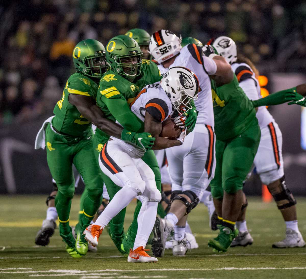 Oregon defenders bring down Oregon State running back Artavis Pierce (#21). The Oregon Ducks defeated the Oregon State Beavers 69 to 10 in the 121st Civil War game at Autzen Stadium in Eugene, Ore. on Saturday November 25, 2017. Photo by Ben Lonergan, Oregon News Lab