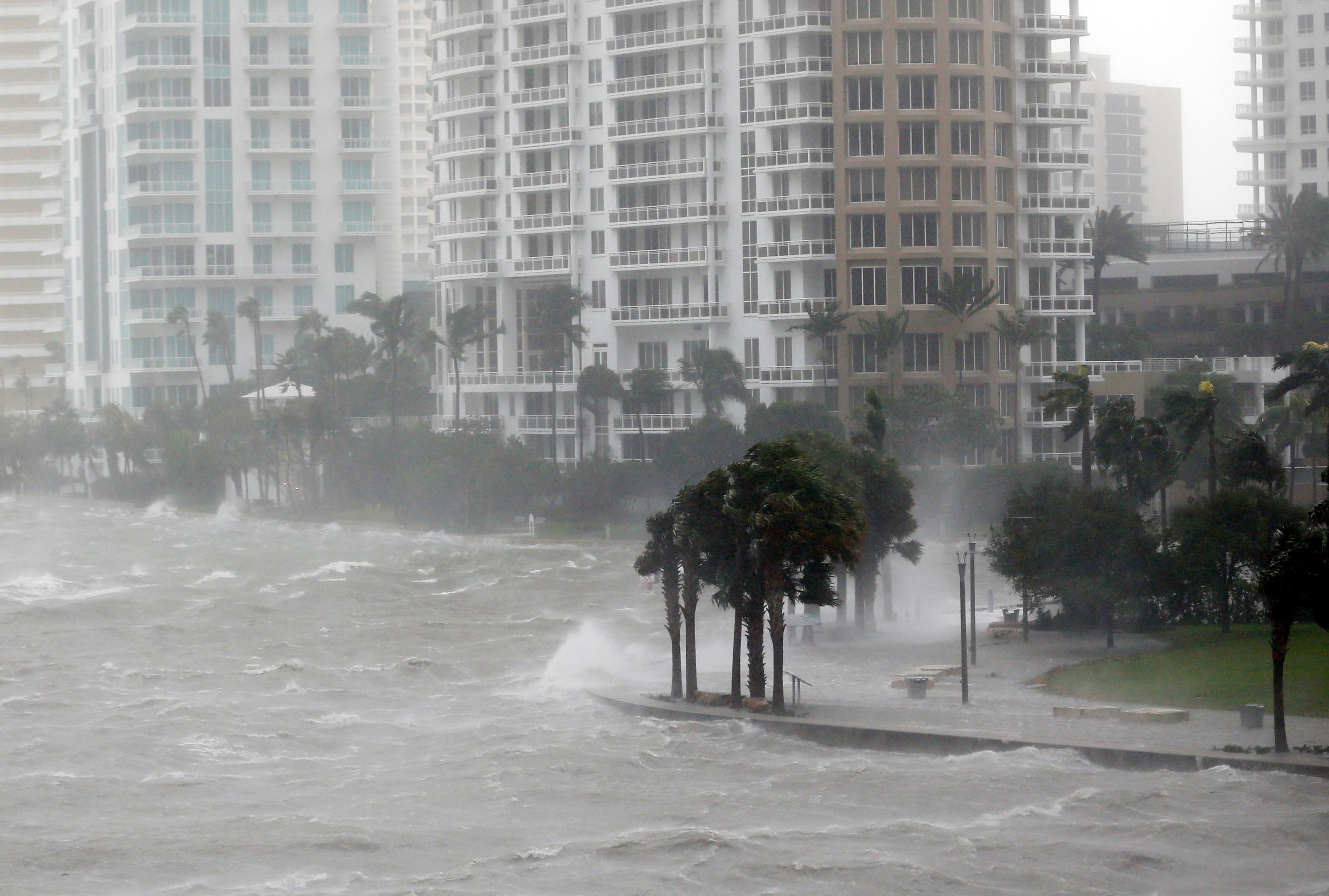 In this Sept. 10, 2017, photo, waves crash over a seawall at the mouth of the Miami River from Biscayne Bay, Fla., as Hurricane Irma passes by in Miami. Rising sea levels and fierce storms have failed to stop relentless population growth along U.S. coasts in recent years, a new Associated Press analysis shows. The latest punishing hurricanes scored bull's-eyes on two of the country's fastest growing regions: coastal Texas around Houston and resort areas of southwest Florida. (AP Photo/Wilfredo Lee)