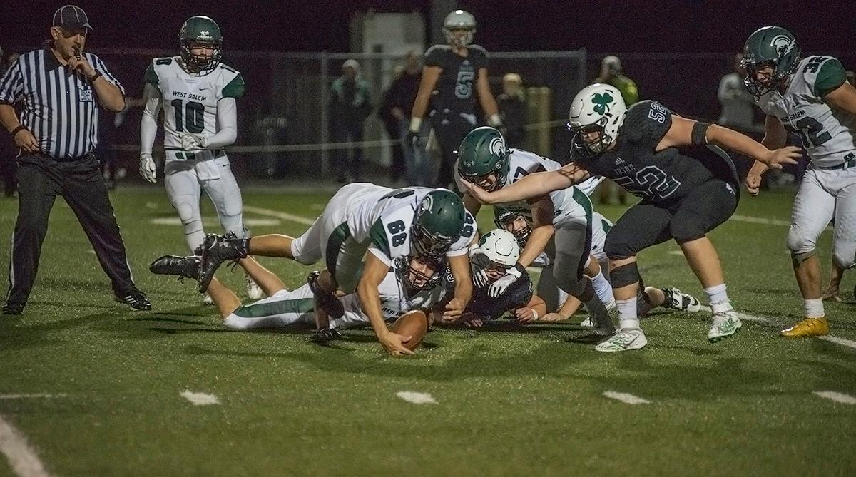 West Salem Titans offensive lineman Seth DeLeon (#68) dives to recover the ball.  On a rainy Monday evening, Sheldon defeated West Salem 41 to 7 at their home field. The game had been postponed from Friday due to unhealthy levels of smoke in the atmosphere from nearby forest fires. Abigail Winn, Oregon News Lab