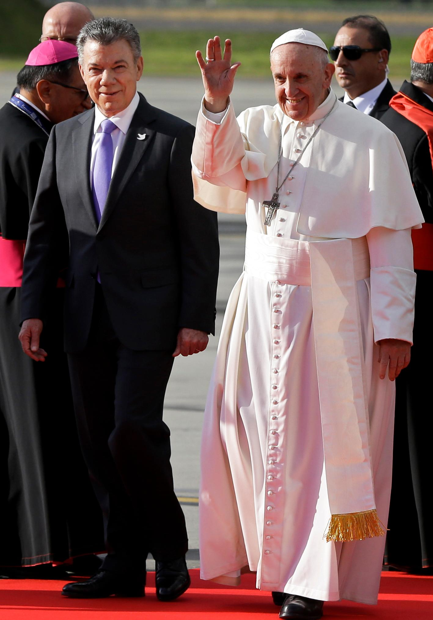 Pope Francis waves next to Colombia's President Juan Manuel Santos as he arrives to El Dorado airport in Bogota, Colombia, Wednesday, Sept. 6, 2017. Pope Francis has arrived in Colombia for a five-day visit. (AP Photo/Ricardo Mazalan)