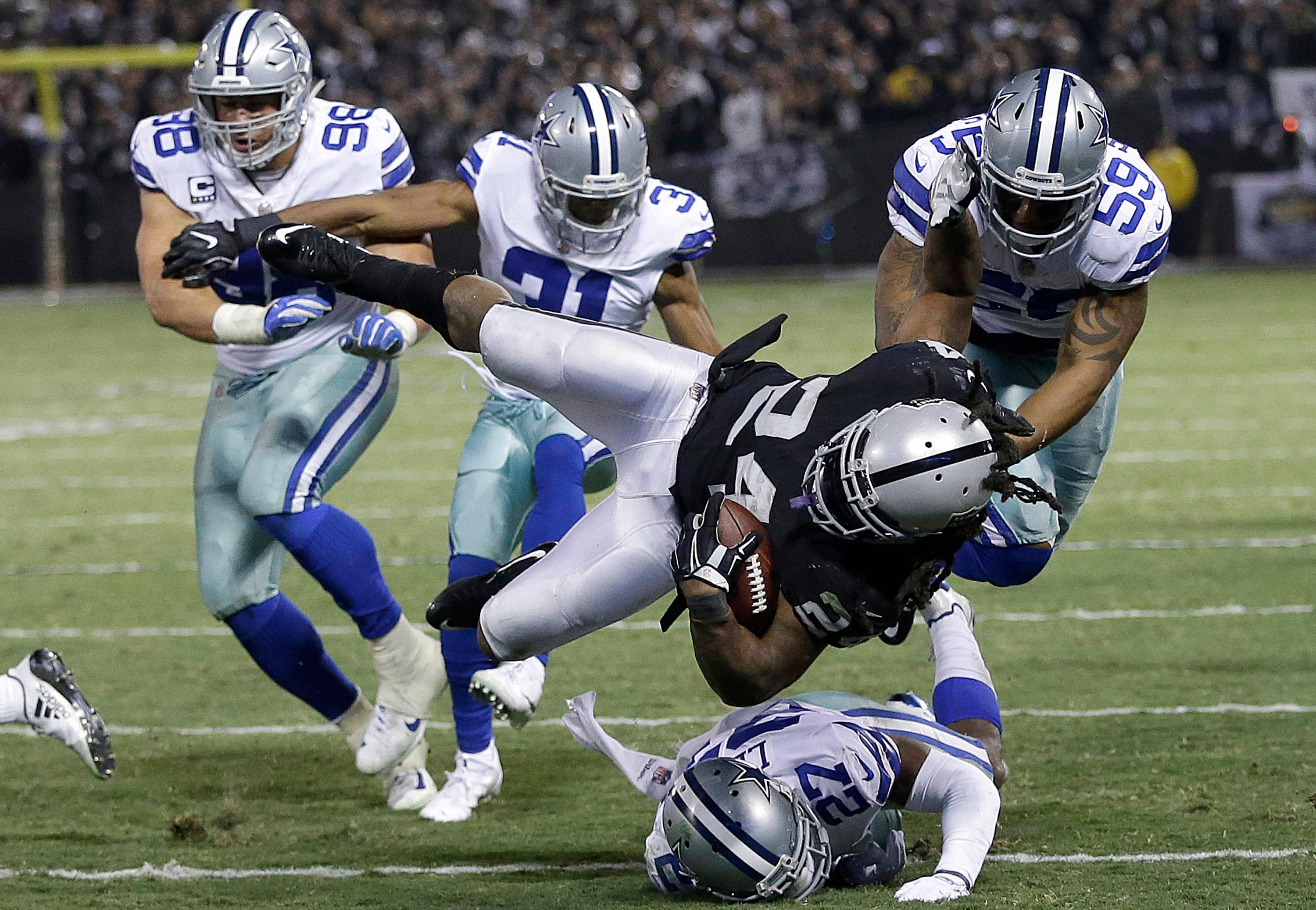 Oakland Raiders running back Marshawn Lynch (24) is tackled by Dallas Cowboys defenders during the second half of an NFL football game in Oakland, Calif., Sunday, Dec. 17, 2017. (AP Photo/Ben Margot)