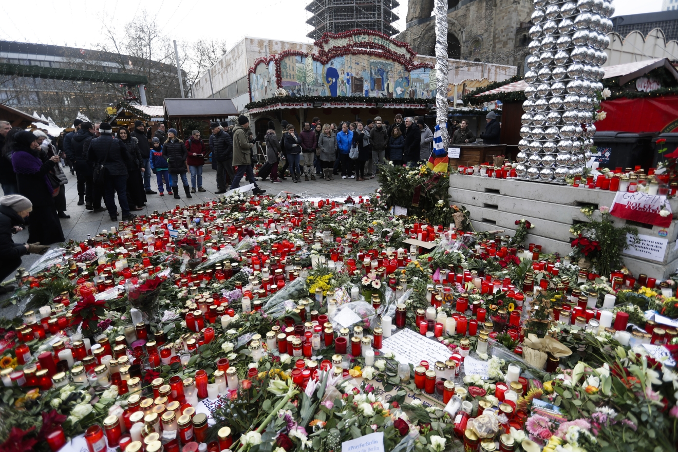 People stand around candles at the reopened Christmas market, three days after a truck ran into the crowd and killed several people, at the Kaiser Wilhelm Memorial Church in Berlin, Thursday, Dec. 22, 2016. (AP Photo/Markus Schreiber)