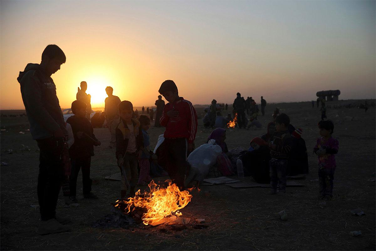 Iraqis who fled the fighting between Iraqi forces and Islamic State militants, gather around flames to warm themselves from the cold wind, as they wait to cross to the Kurdish controlled area, in the Nineveh plain, northeast of Mosul, Thursday, Nov. 17, 2016. Cloudy skies neutralized air power in Mosul on Thursday, Iraqi forces said, hampering their advance into the northern city, although they still faced deadly attacks by Islamic State militants that killed seven civilians and two soldiers. (AP Photo/Hussein Malla)