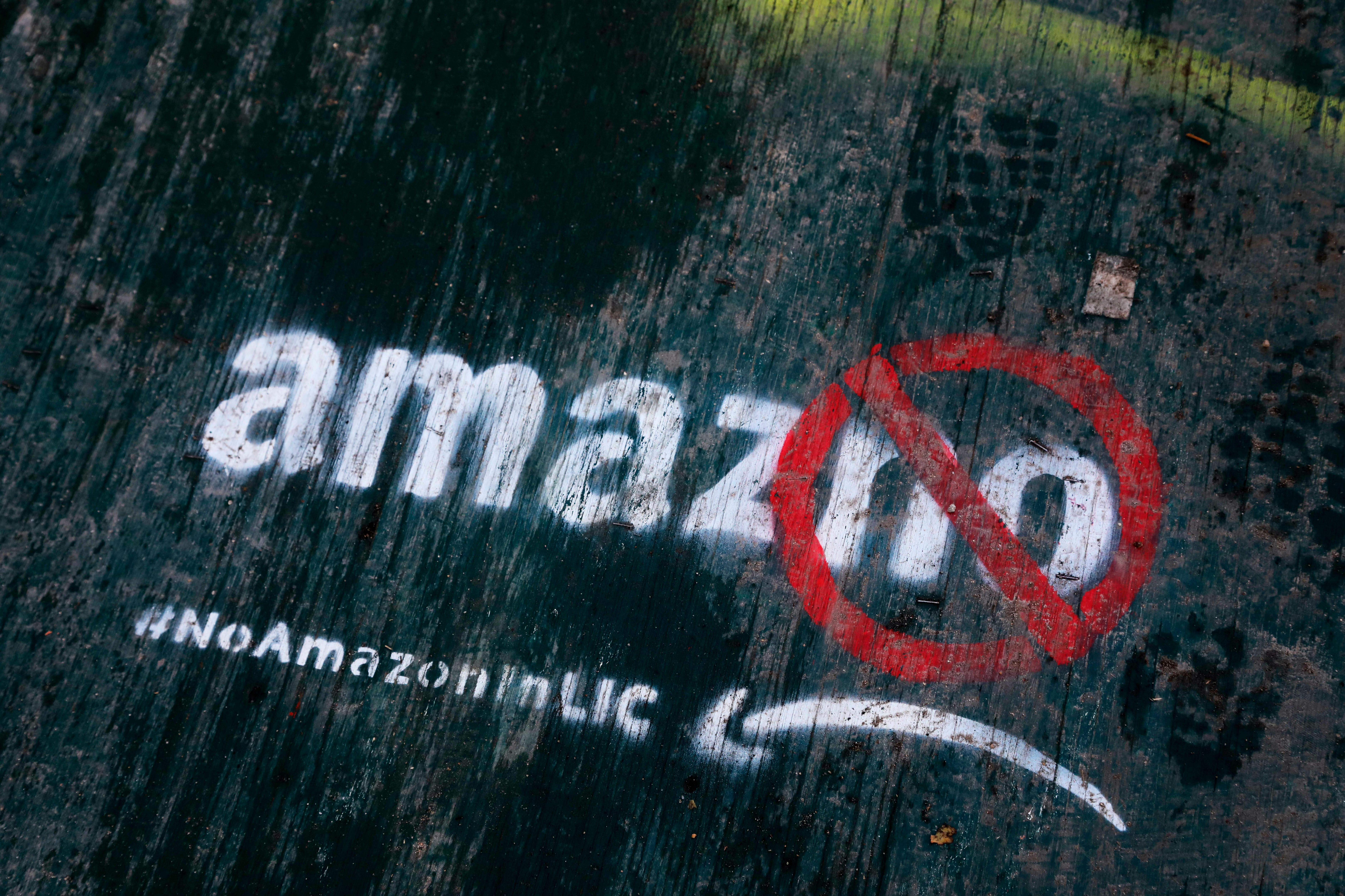 FILE - In this Nov. 16, 2018, file photo graffiti has been painted on a sidewalk by someone opposed to the location of an Amazon headquarters in the Long Island City neighborhood in the Queens borough of New York. (AP Photo/Mark Lennihan, File)