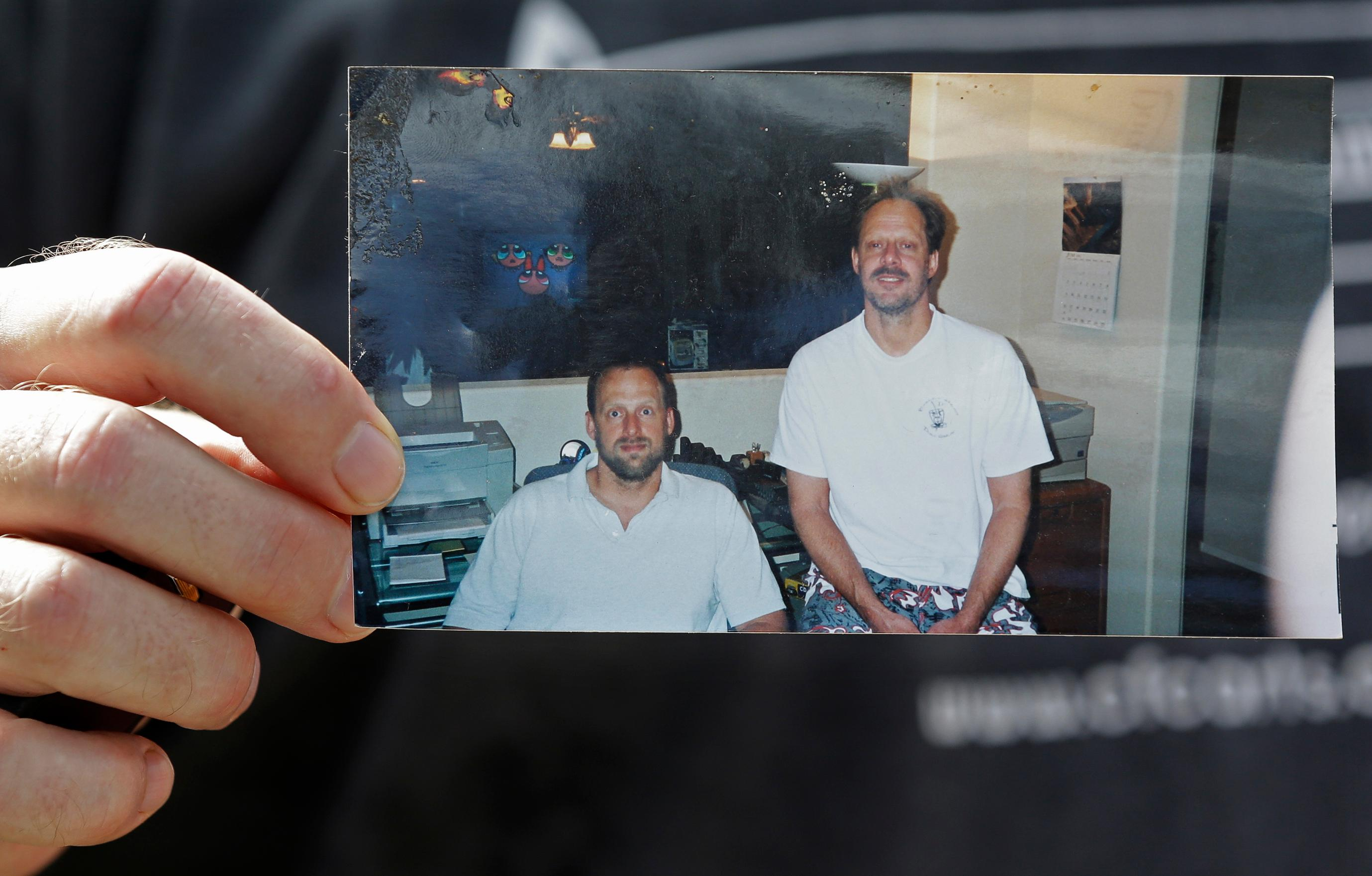 Eric Paddock holds a photo of him, at left, and his brother, Stephe