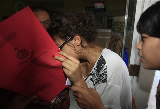 Heather Mack, covering her face, is led to a hospital for a medical check by Indonesian police officers in relation to the death of her mother Sheila von Wiese-Mack in Bali, Indonesia.