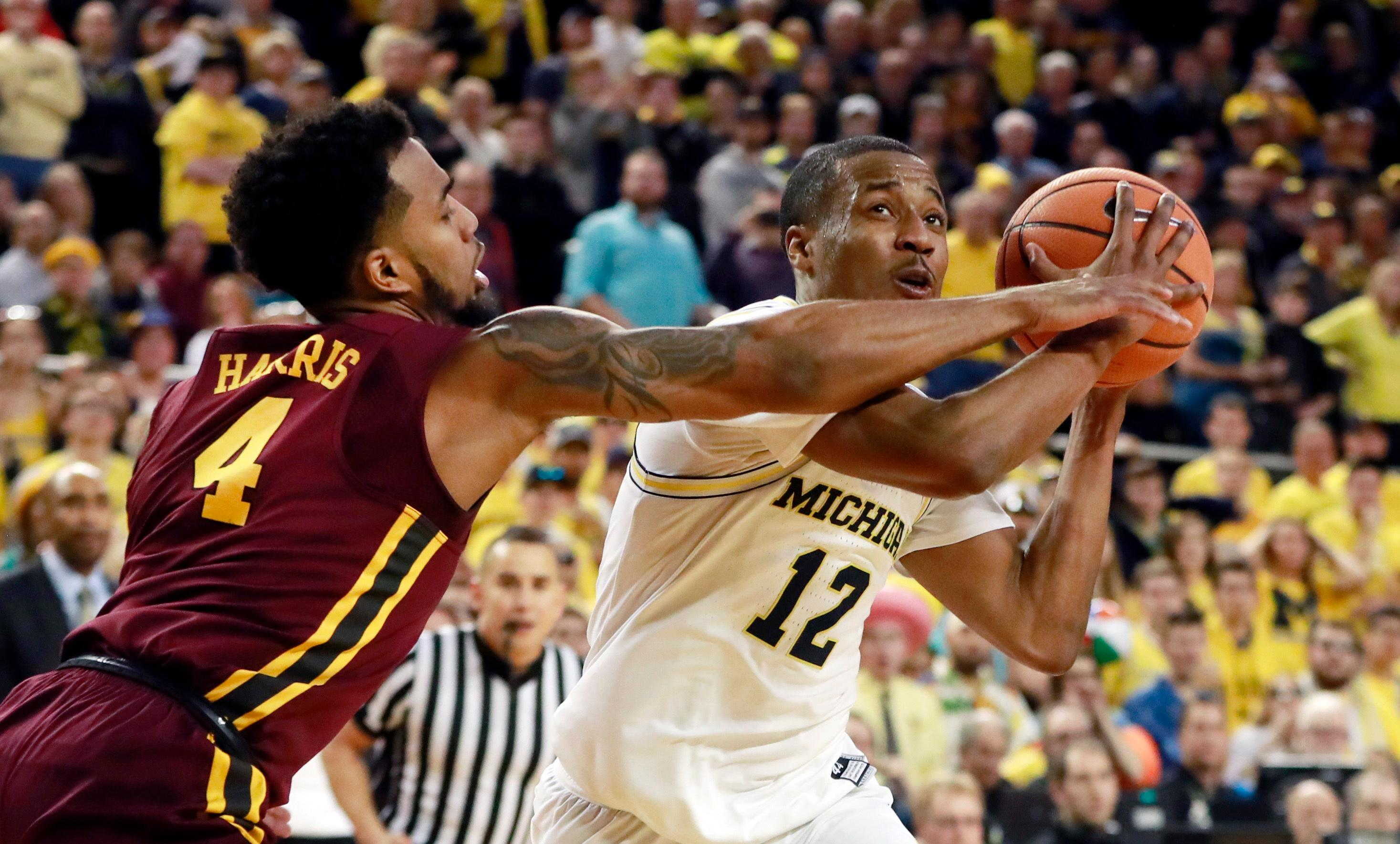 Michigan guard Muhammad-Ali Abdur-Rahkman (12) is fouled by Minnesota guard Jamir Harris (4) during overtime of an NCAA college basketball game, Saturday, Feb. 3, 2018, in Ann Arbor, Mich. (AP Photo/Carlos Osorio)