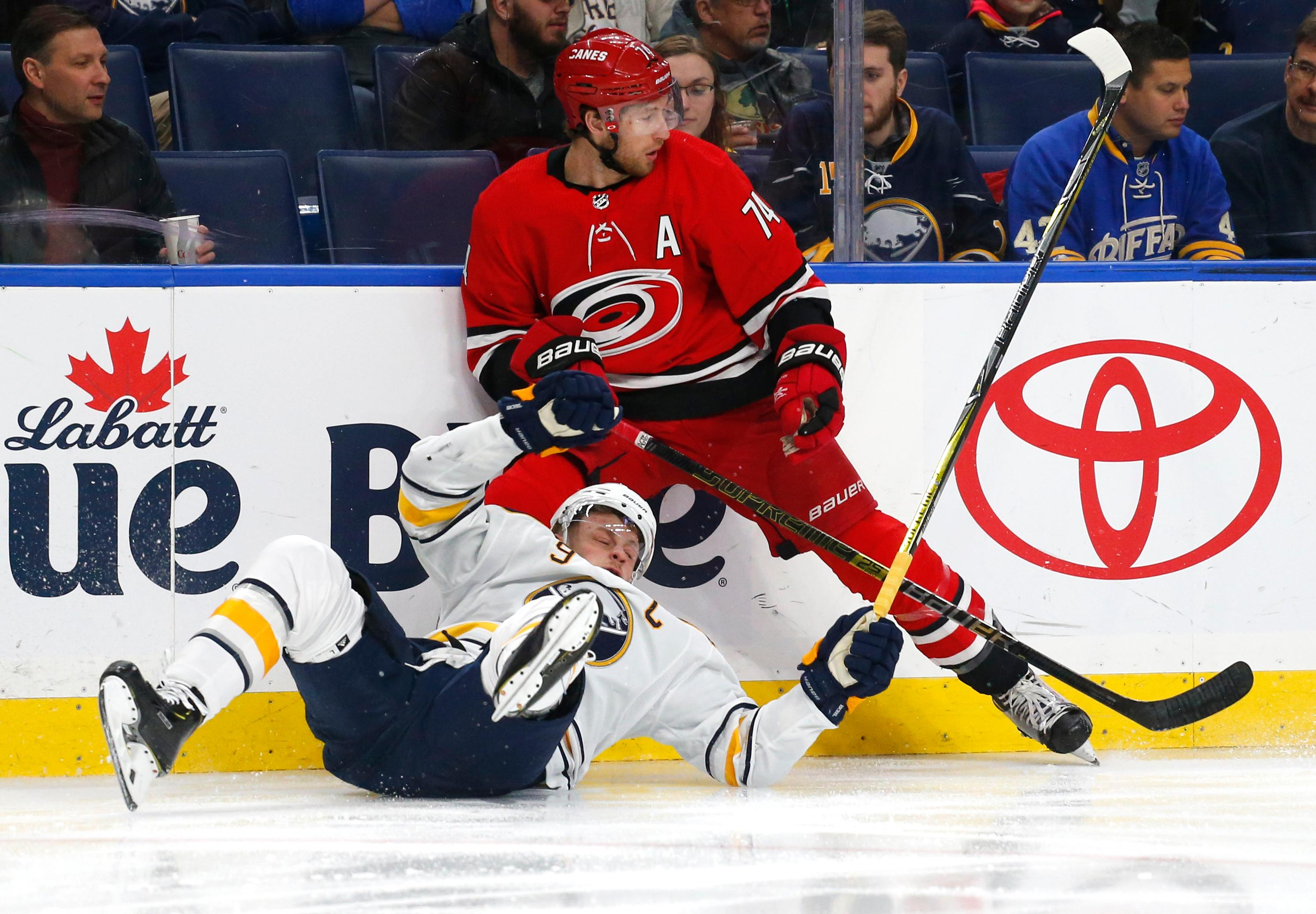 Buffalo Sabres forward Jack Eichel (9) and Carolina Hurricanes defenseman Jaccob Slavin (74) collide during the first period of an NHL hockey game Thursday, Feb. 7, 2019, in Buffalo N.Y. (AP Photo/Jeffrey T. Barnes)