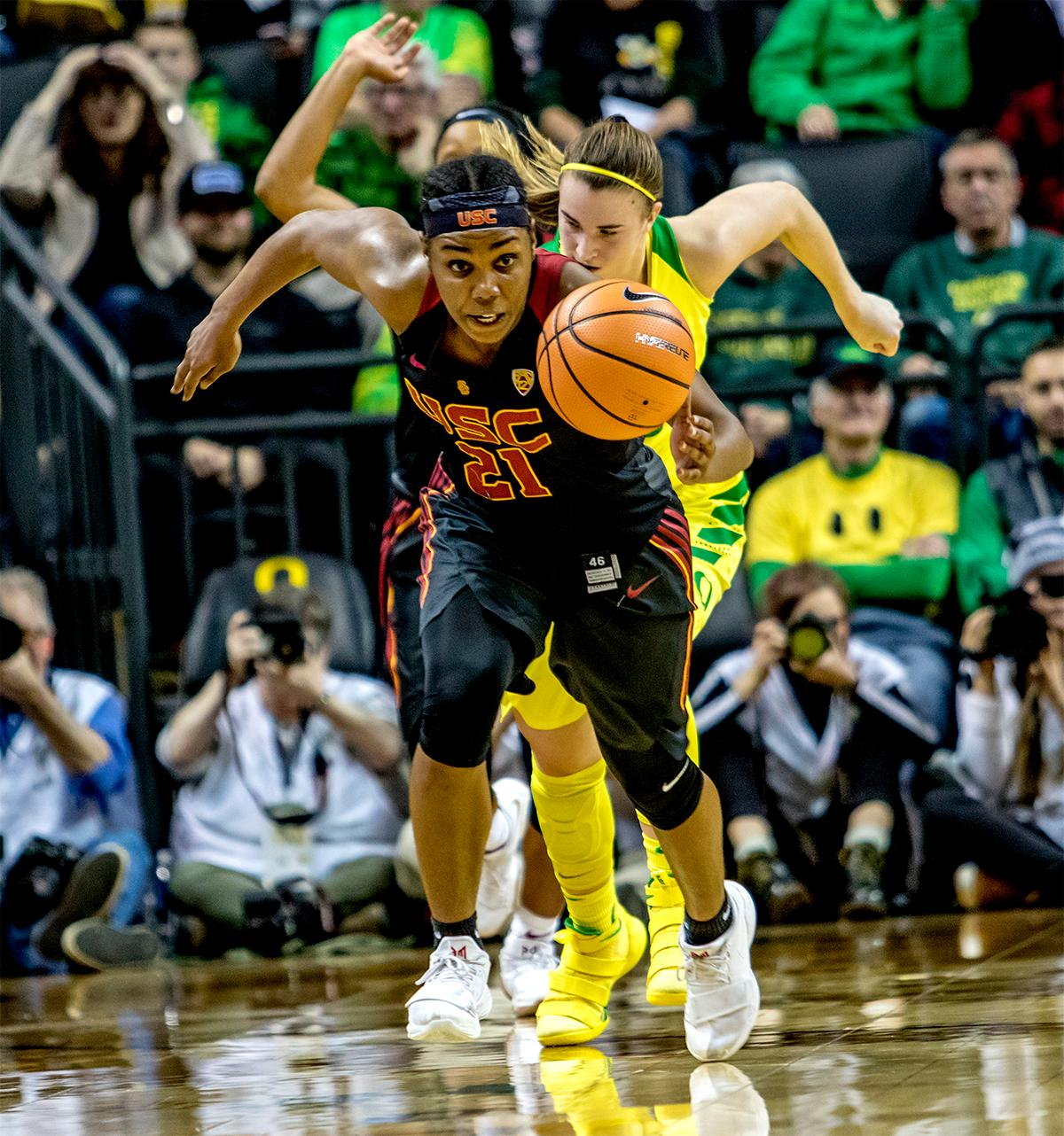 The Trojan's Aliya Mazyck (#21) runs the ball down the court after a steal. The Oregon Ducks defeated the USC Trojans 80-74 on Friday at Matthew Knight Arena in a  game that went into double overtime. Lexi Bando sealed the Ducks victory by scoring a three-pointer in the closing of the game. Ruthy Hebard set a new NCAA record of 30 consecutive field goals, the old record being 28. Ruthy Hebard got a double-double with 27 points and 10 rebounds, Mallory McGwire also had 10 rebounds. The ducks had four players in double digits. The Ducks are now 24-4, 13-2 in the Pac-12, and are tied for first with Stanford. Photo by August Frank, Oregon News Lab