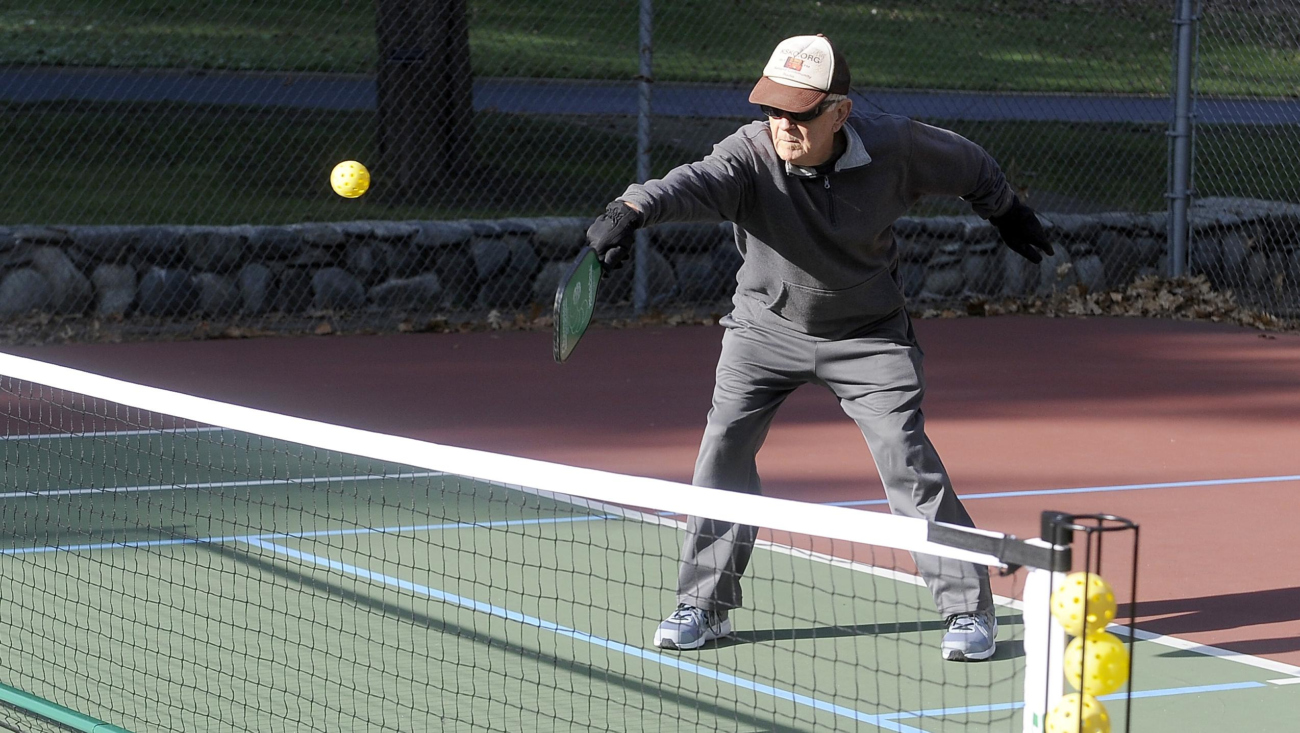Bob Valine makes a hit over the net playing a match of pickleball in Lithia Park. [Mail Tribune / Andy Atkinson]