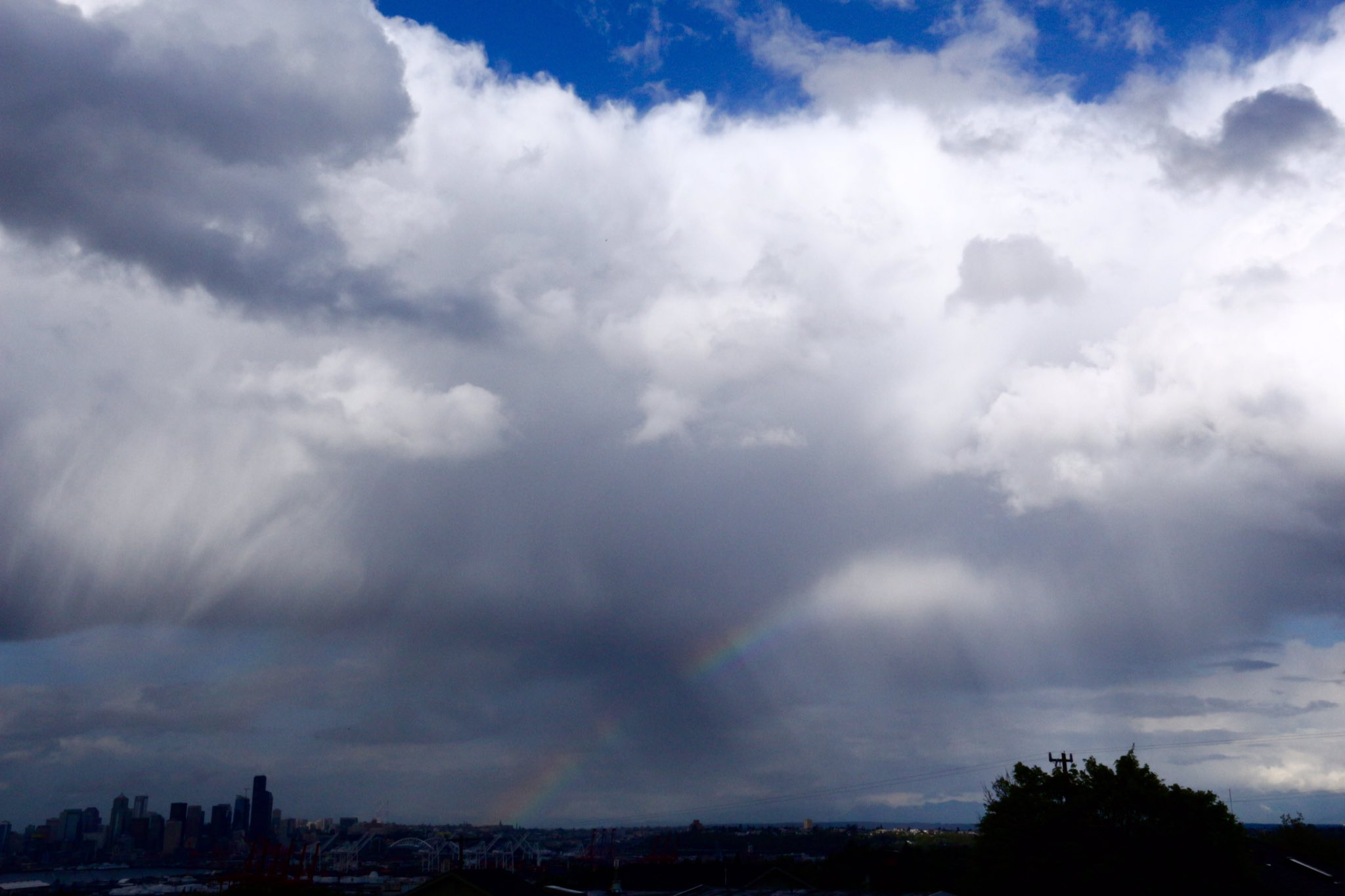 Storm clouds and a rainbow are seen over Seattle, Tuesday, April 18, 2017. (Photo: Kevin Freitas)