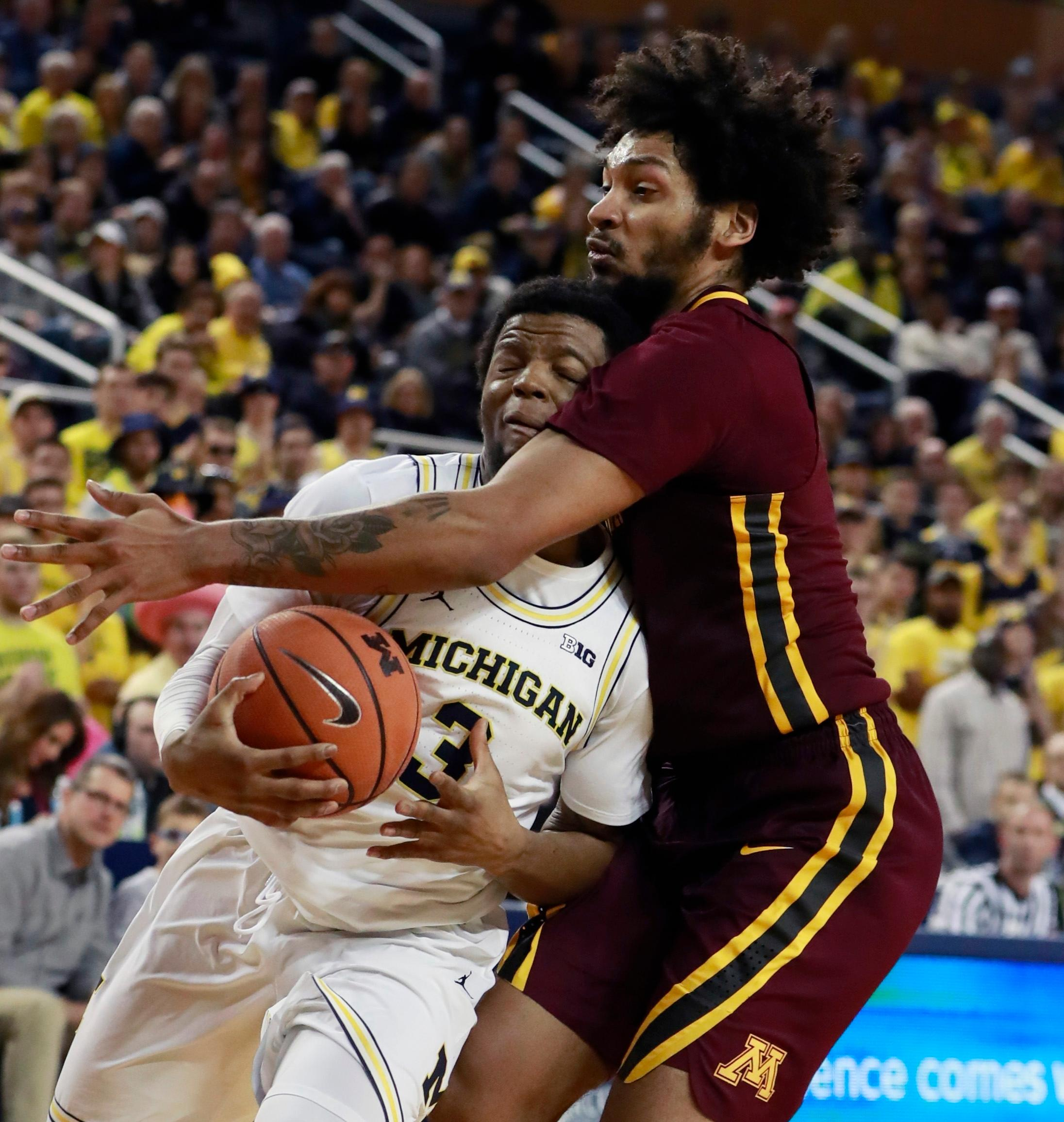 Michigan guard Zavier Simpson (3) is fouled by Minnesota forward Jordan Murphy during the second half of an NCAA college basketball game, Saturday, Feb. 3, 2018, in Ann Arbor, Mich. (AP Photo/Carlos Osorio)