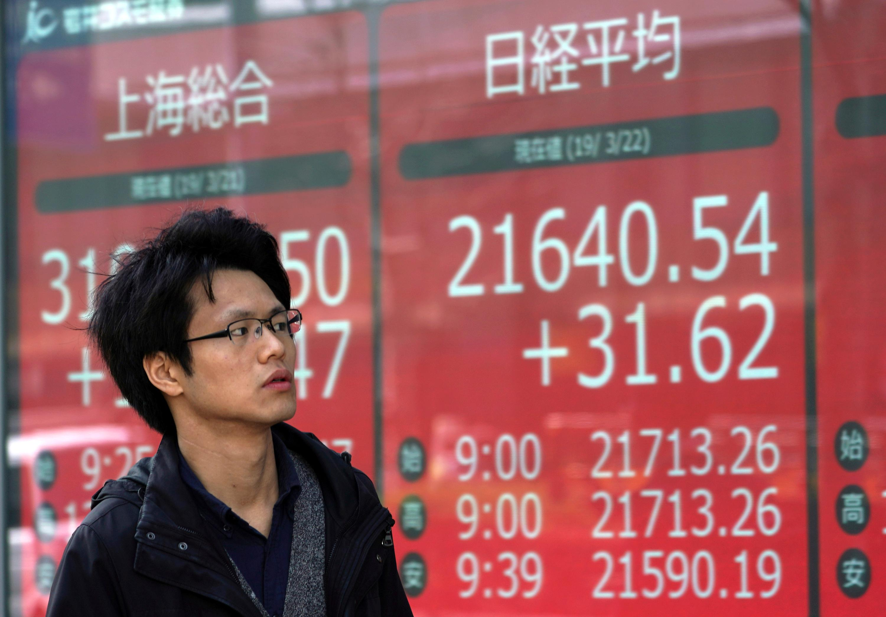 A man walks past an electronic stock board showing Japan's Nikkei 225 index at a securities firm in Tokyo Friday, March 22, 2019.{ } (AP Photo/Eugene Hoshiko)