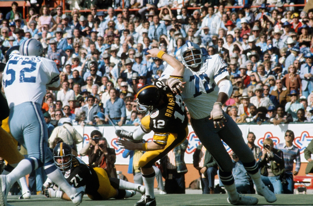 "Ed ""Too Tall"" Jones of the Dallas Cowboys tackles Terry Bradshaw of the Pittsburgh Steelers during Super Bowl XIII at the Orange Bowl on Jan. 21, 1979 in Miami.  The Steelers won, 35-31. (Photo by Focus On Sport/Getty Images)"