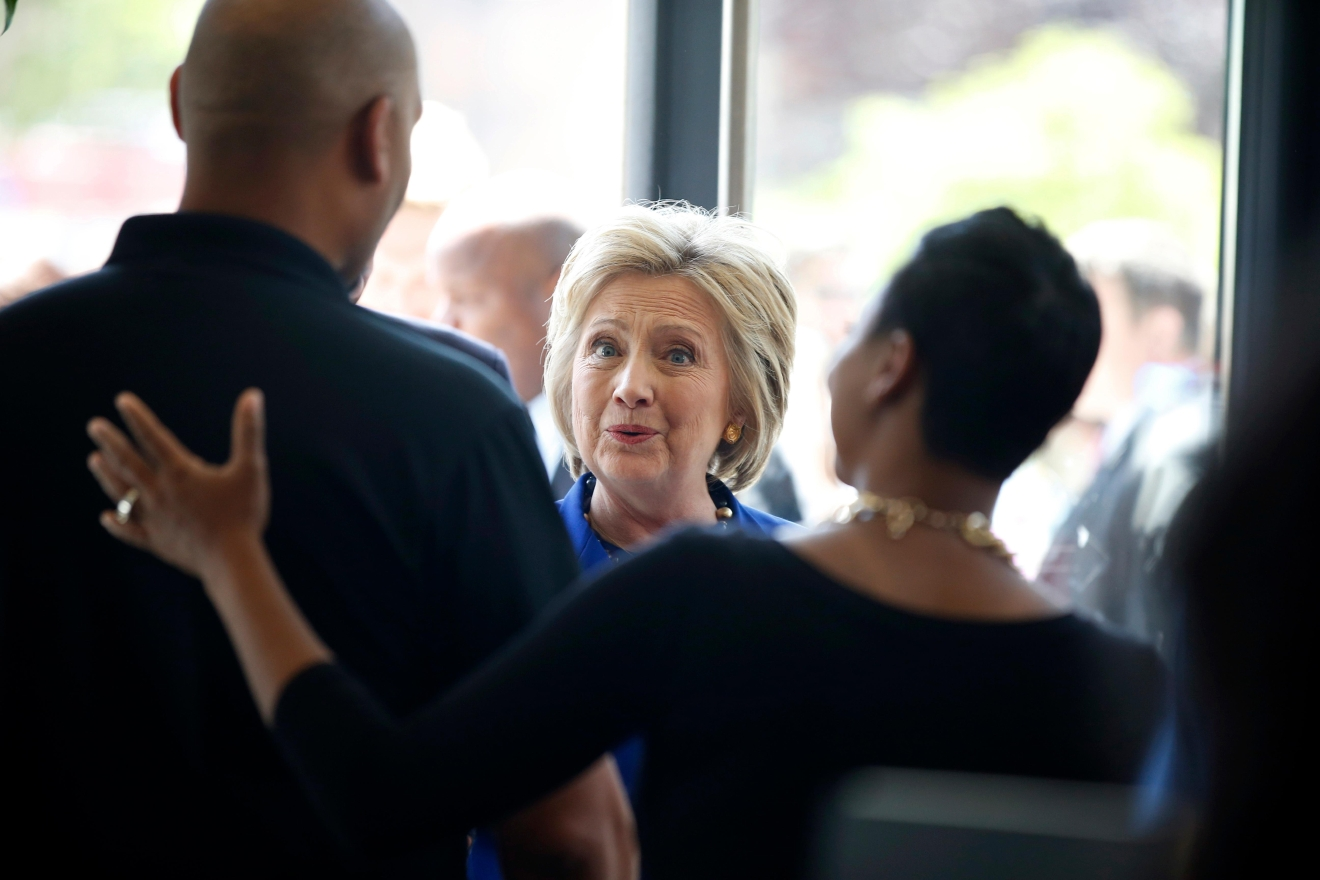 Democratic presidential candidate Hillary Clinton is greeted by Donnie Simpson, left, owner of Uprising Muffin Company, during a stop at the store, Friday, June 10, 2016, in Washington. (AP Photo/Alex Brandon)