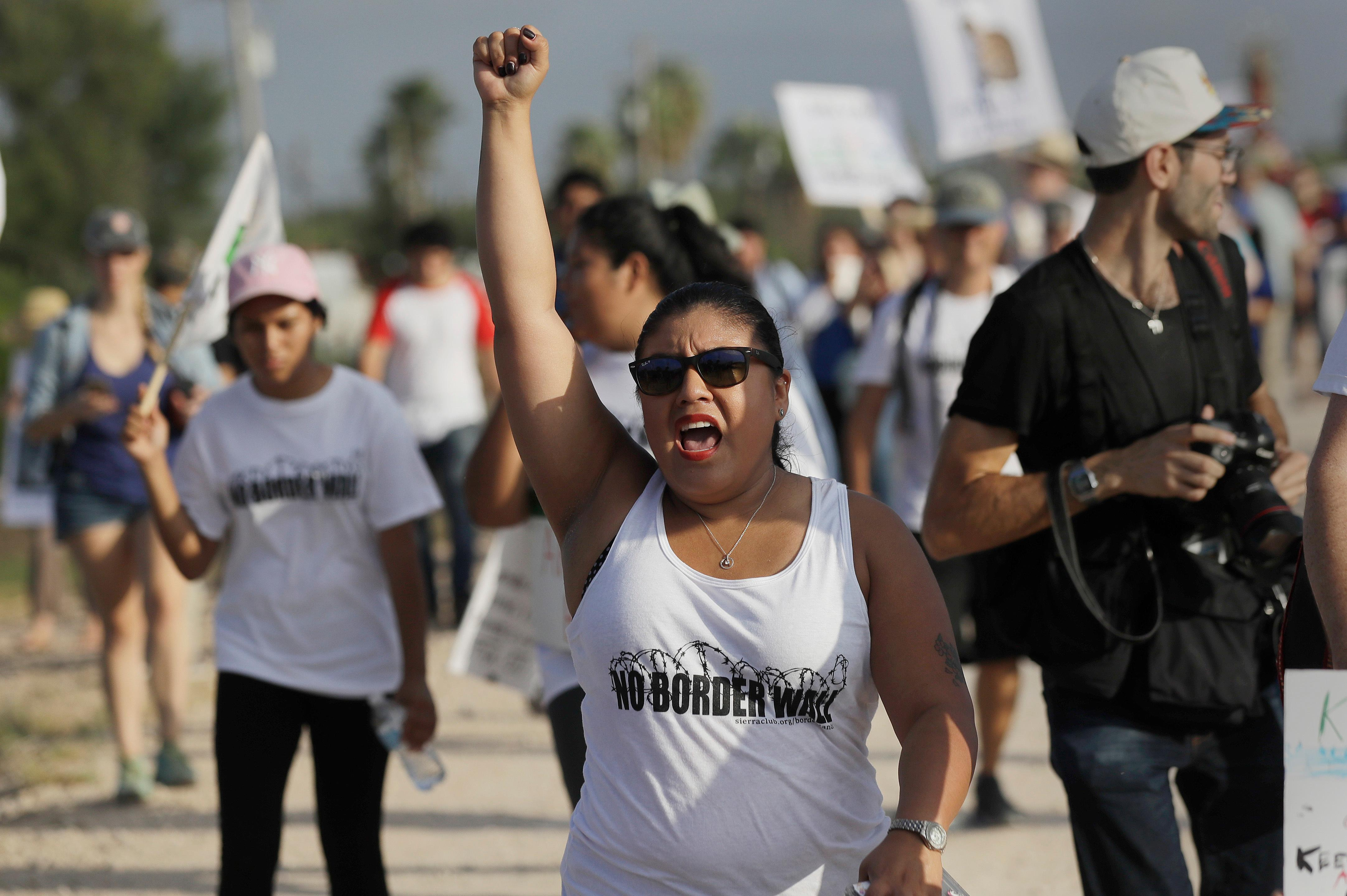 Diane Landers raises her fist as she chants during a march along a levee toward the Rio Grande to oppose the wall the U.S. government wants to build on the river separating Texas and Mexico, Saturday, Aug. 12, 2017, in Mission, Texas. The area would be the target of new barrier construction under the Trump administration's current plan. (AP Photo/Eric Gay)