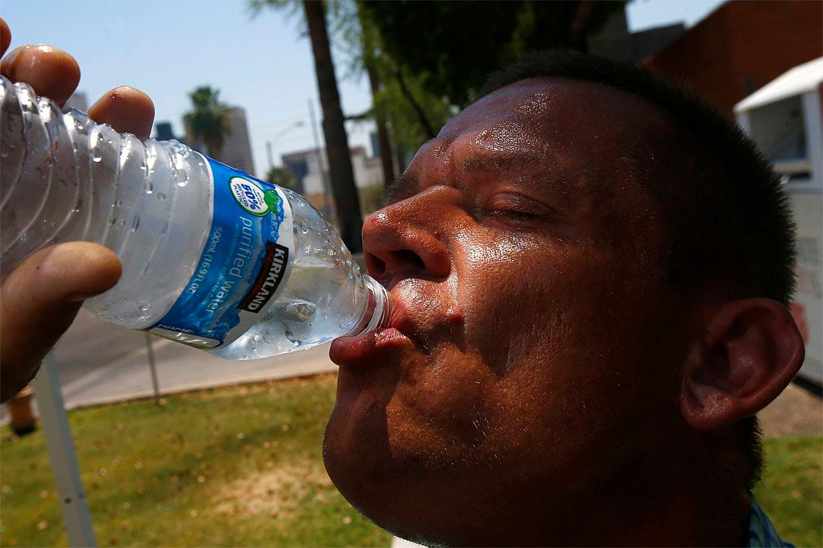 Steve Smith takes a drink of water as he tries to keep hydrated and stay cool as temperatures climb to near-record highs, Monday, June 19, 2017, in Phoenix. (AP Photo/Ross D. Franklin)
