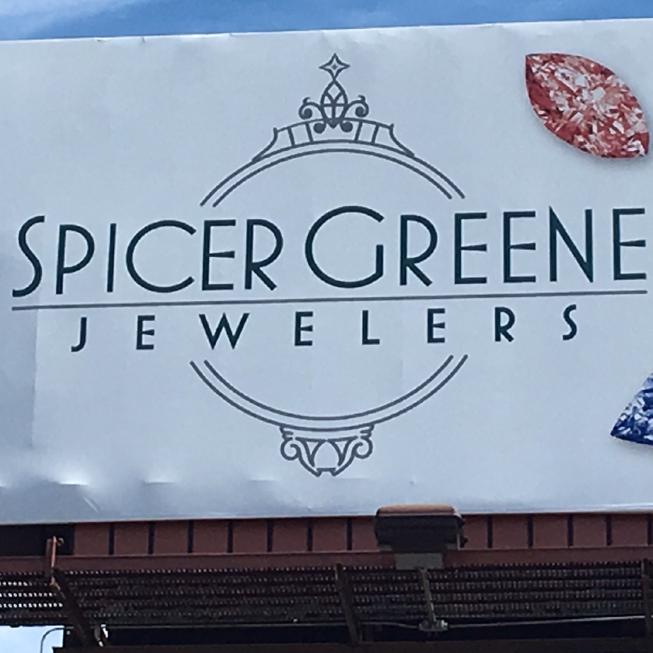"Spicer-Greene Jewelers rented a billboard that says ""Sometimes, it's ok to throw rocks at girls..."" The words are written on a white background, surrounded by pictures of colorful gemstones. (Photo credit: WLOS Staff)"